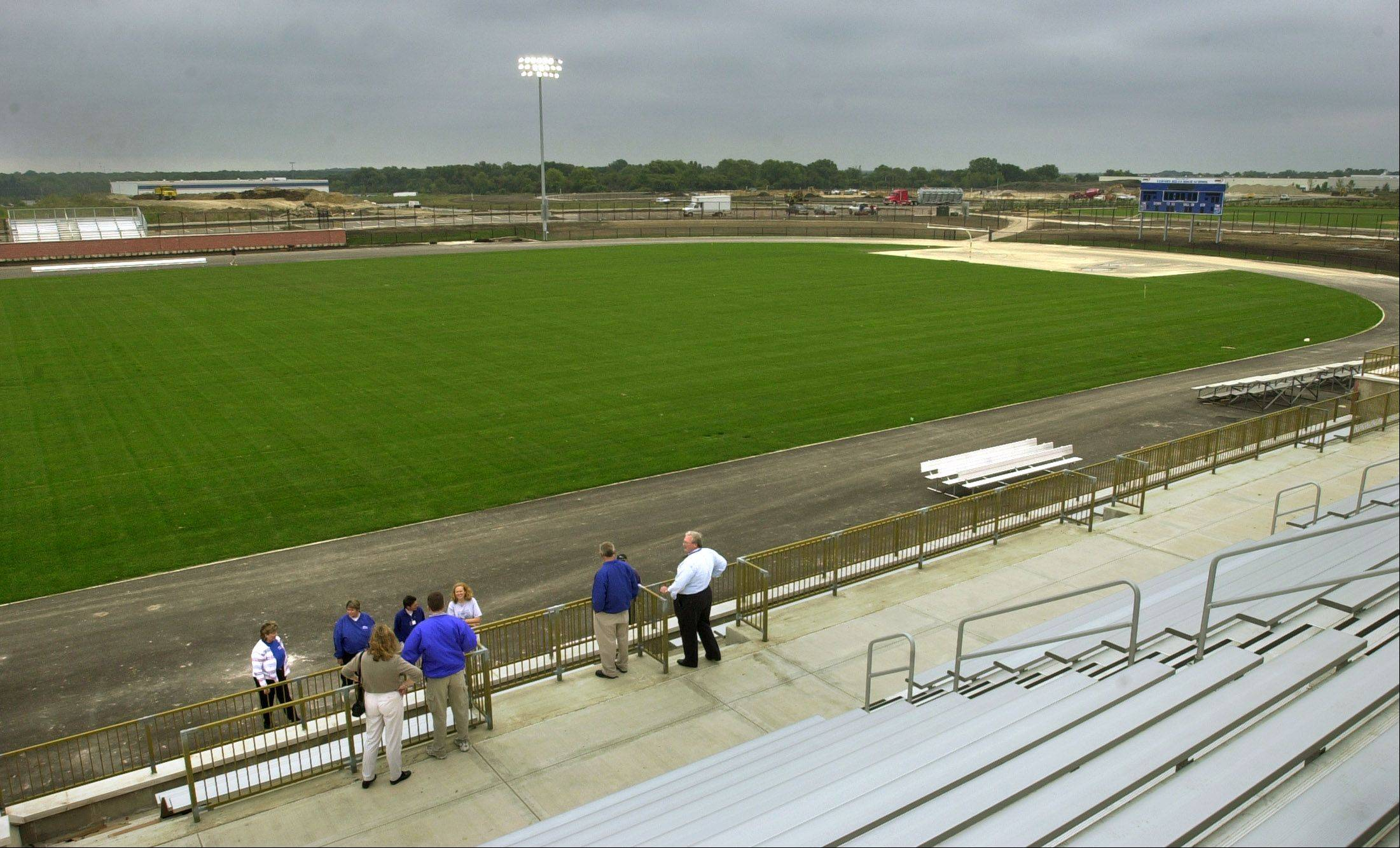 Vernon Hills High School officials look over the new football field in 2002. Now, a volunteer group is raising money to replace the grass with artificial turf.