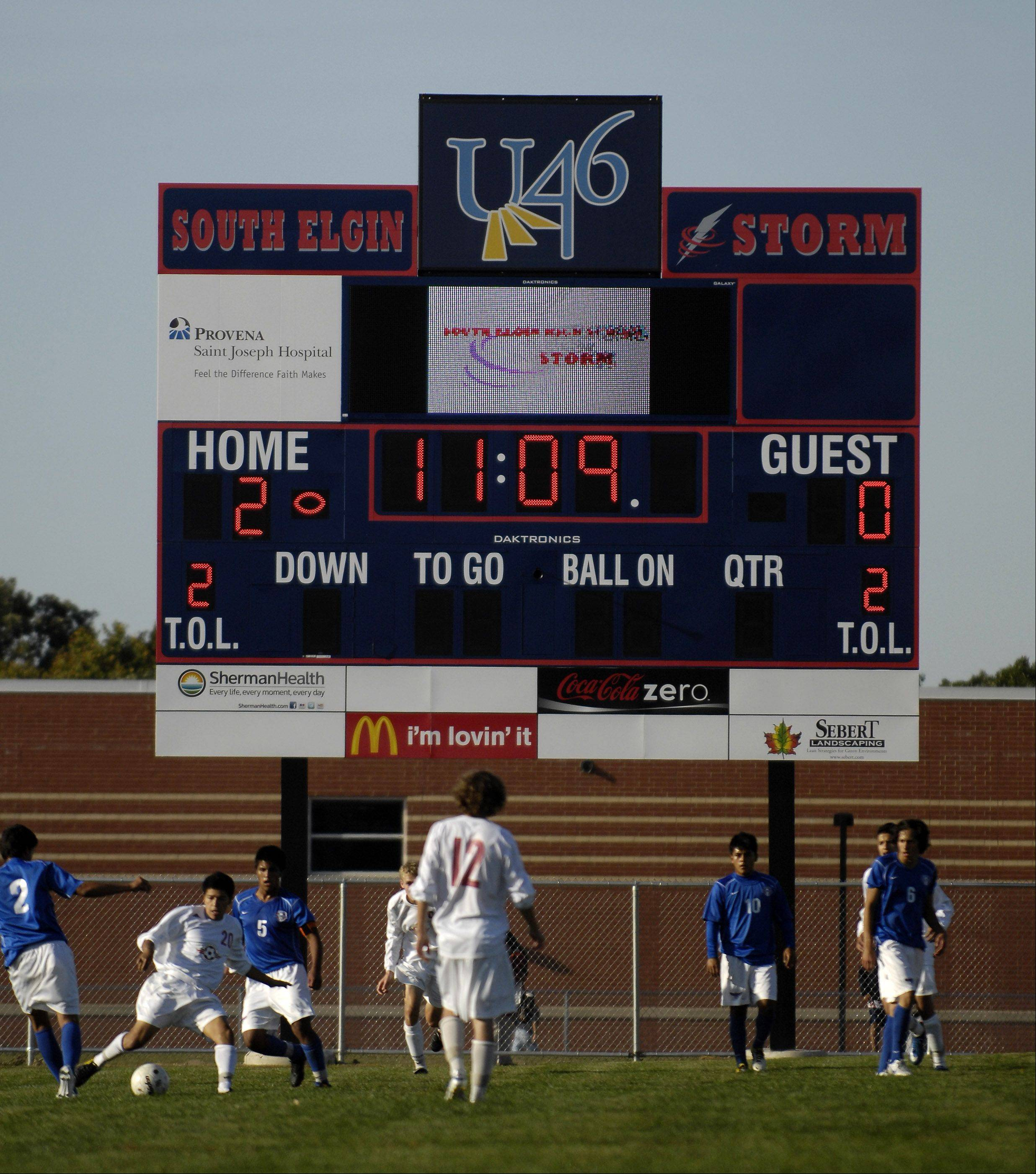 Glenbard District 87 officials are considering whether to put advertising on the scoreboards at some of its high schools. Other suburban schools already have similar arrangements. The stadium scoreboard at South Elgin High School, above, displays the names of sponsors.