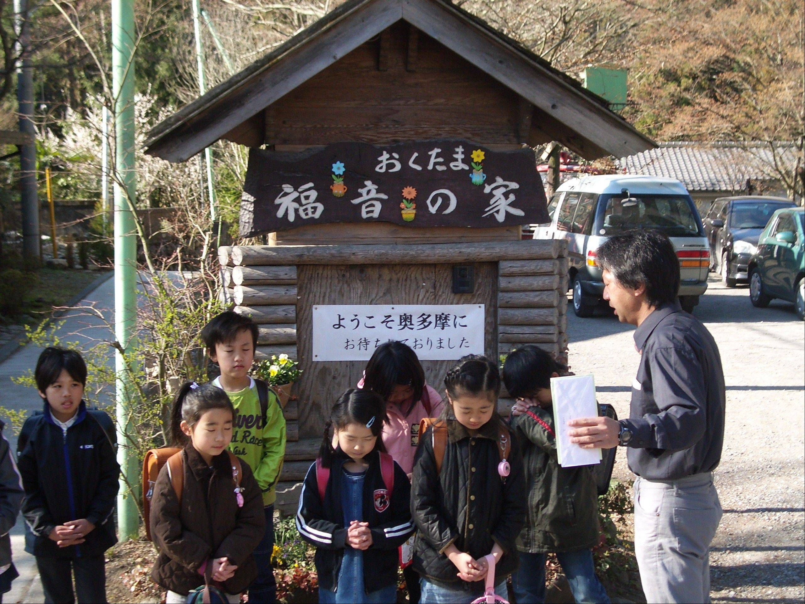Rev. Akira Sato talks with children in his congregation at the retreat center where they are living.