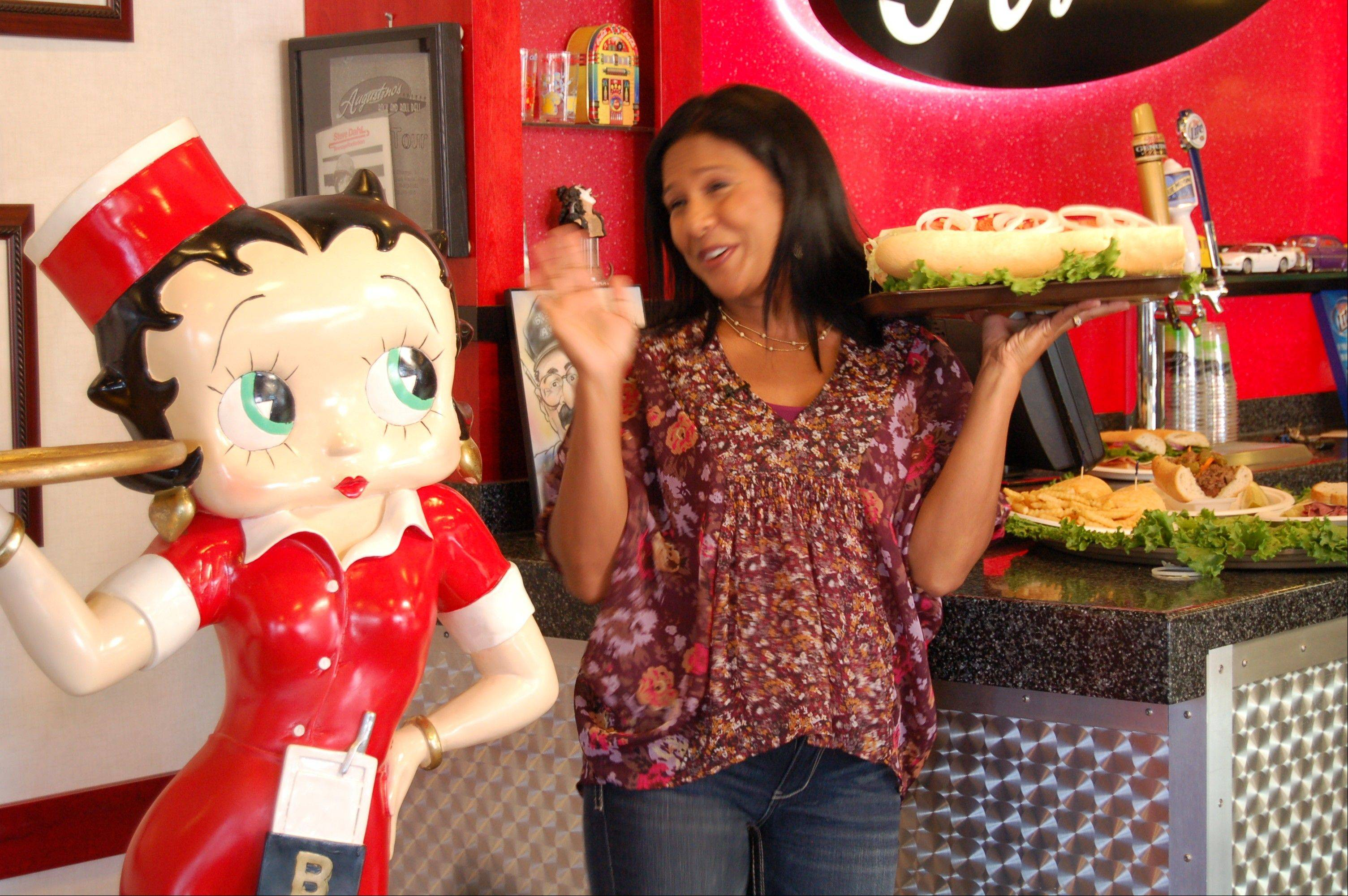"Eva Saha of ABC 7's ""190 North"" poses with Betty Boop and a platter of Augustino's Rock and Roll Deli sandwiches."