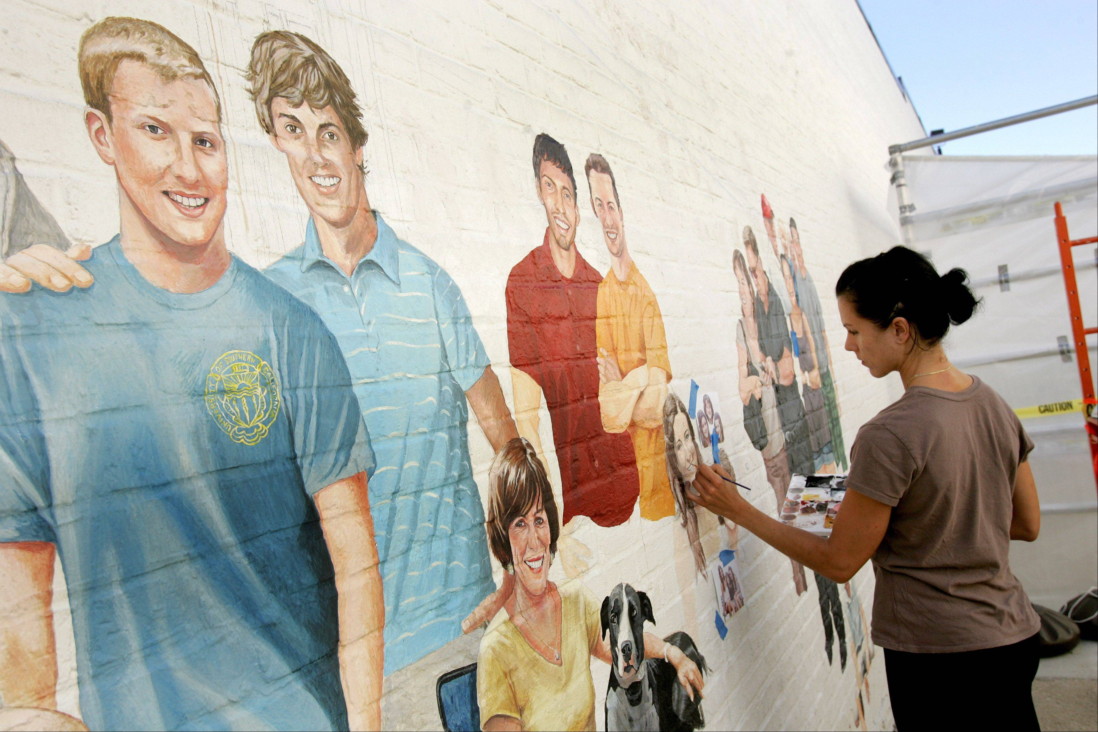 "Adela Vystejnova paints a family in the ""Naperville Loves a Parade"" mural in downtown Naperville."