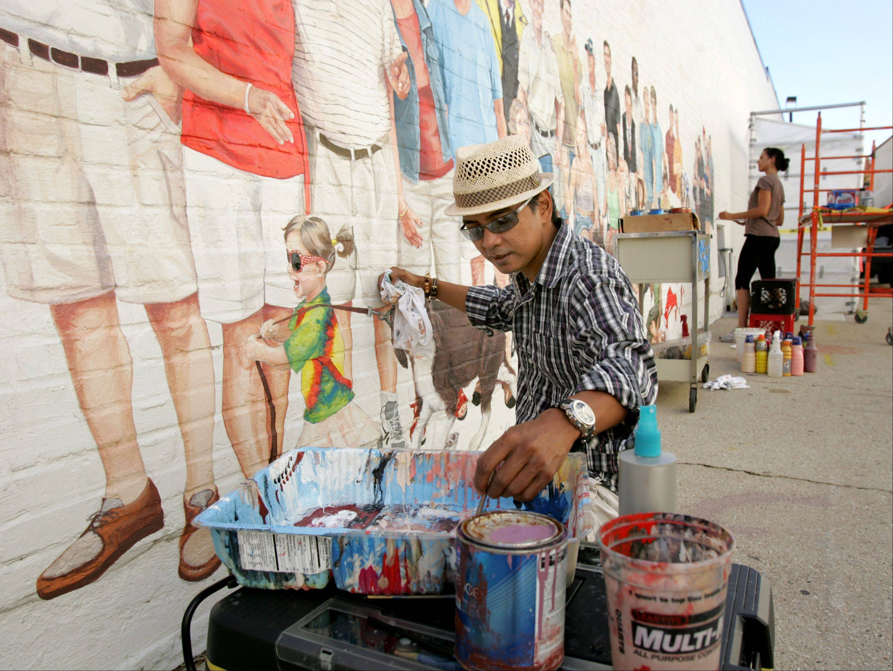 "Diosdado ""Dodie"" Mondero paints the ""Naperville Loves a Parade"" mural in downtown Naperville. ""It's a fun and exciting project,"" he said. ""I'm working with such a great team."" Mondero and three other artists started working on the project in April of this year. The mural features portraits of Naperville residents."