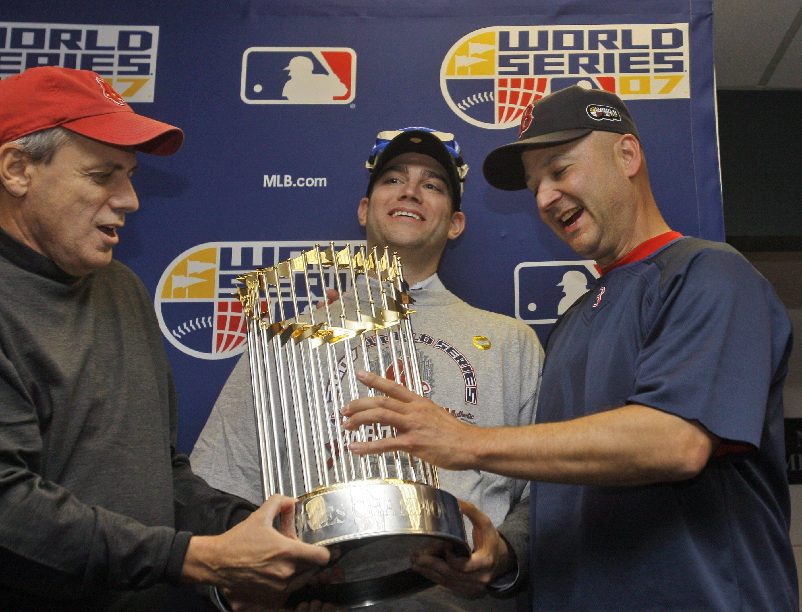Triumphant trio dismantled. Boston Red Sox president Larry Lucchino, left, general manager Theo Epstein, and manager Terry Francona were all smiles as they held the World Series trophy after Boston beat the Colorado Rockies on Oct. 28, 2007 in Denver to sweep the series. Now only Lucchino remains with the franchise with Francona stepping down and Epstein headed to Chicago to run the Cubs.