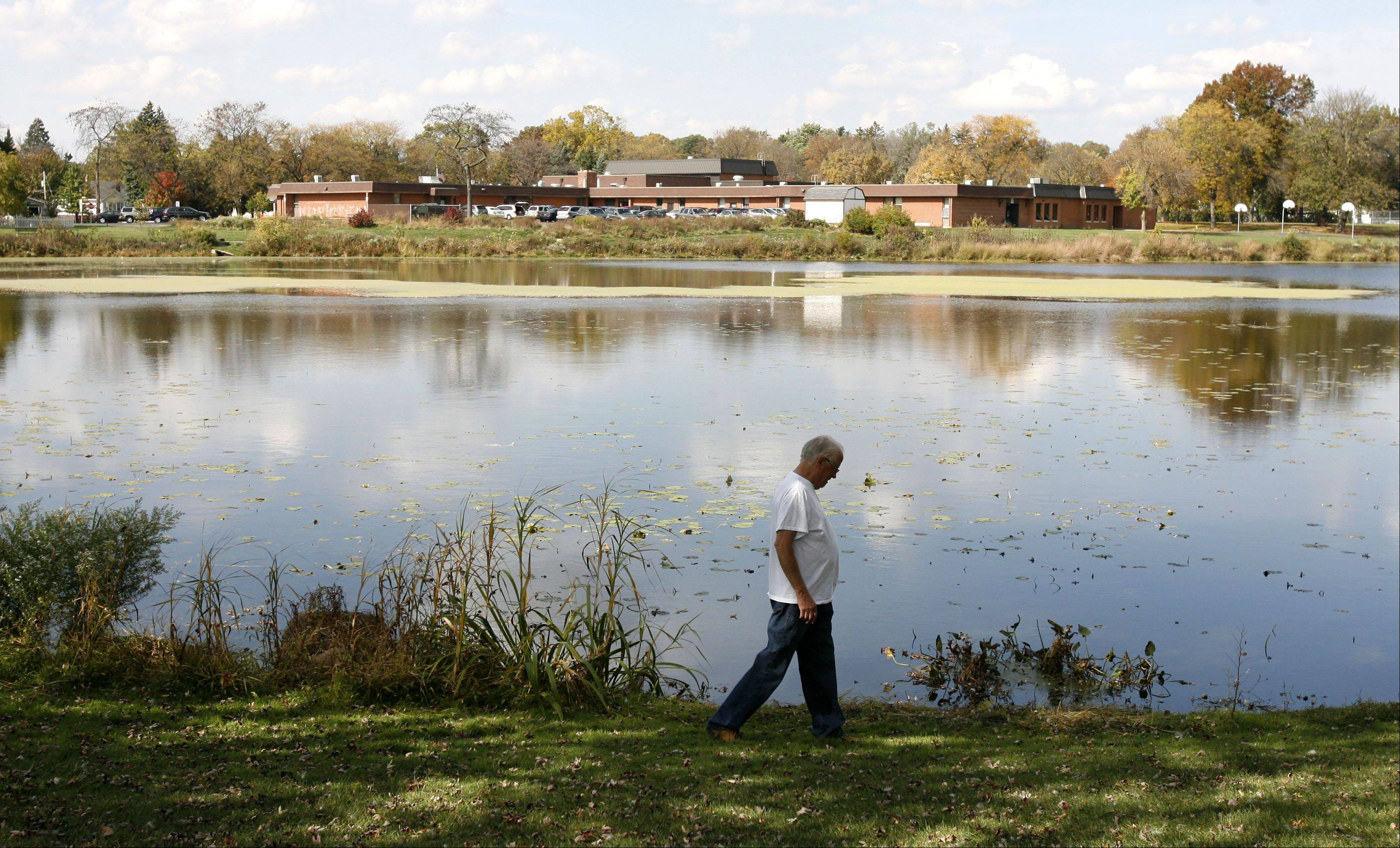 Donald Easterbrook of Lombard walks the shore of Terrace View Pond in Lombard. As the village and the park district are considering seven options to increase the pond's stormwater capacity, Easterbrook said he is concerned the pond's environment may be harmed.