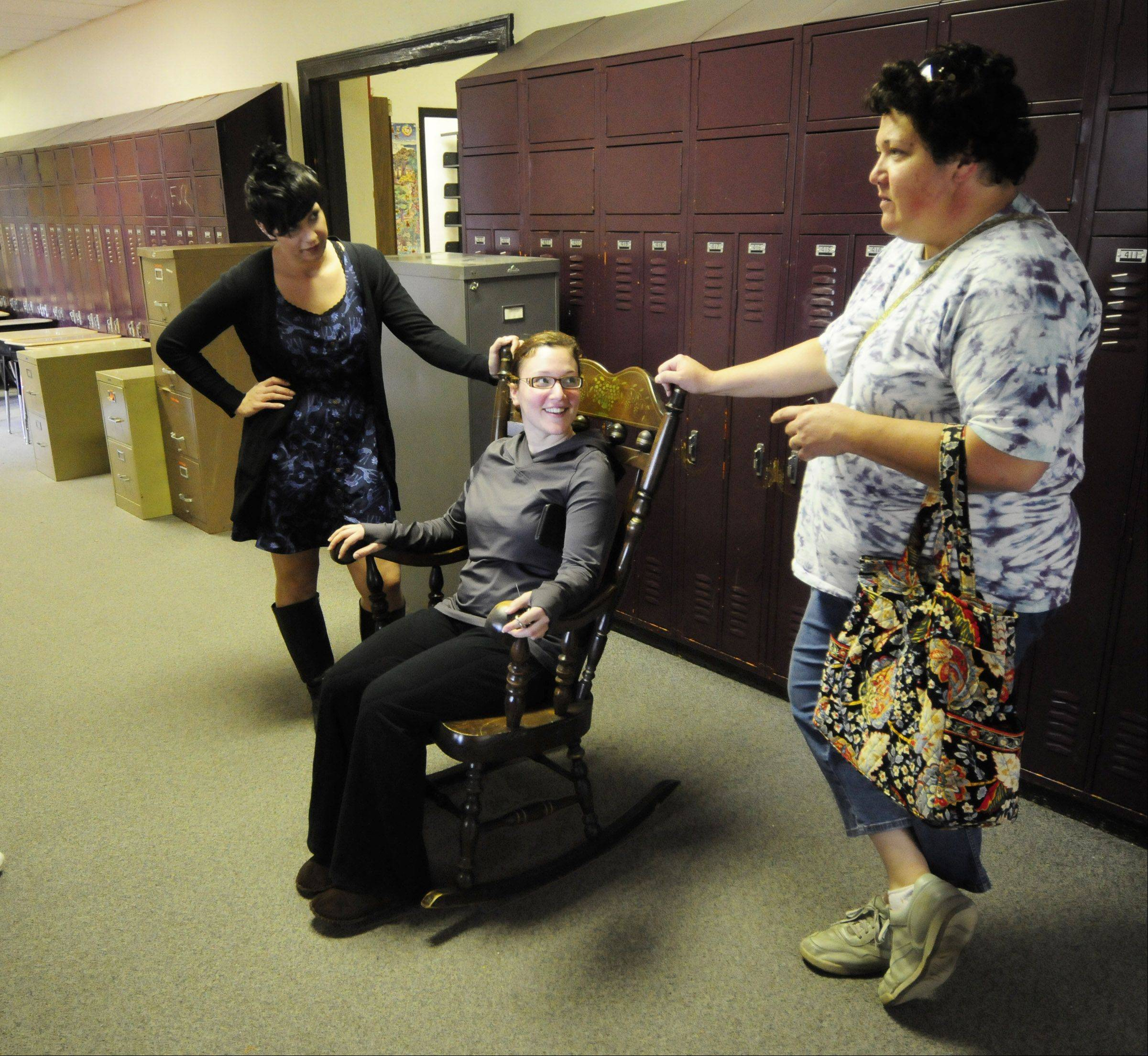 Meg Houser tries out a rocking chair she found for $5. After conferring with her sister Coby Houser, left, and mother Carol Houser, she decided it was a deal too good to pass up.