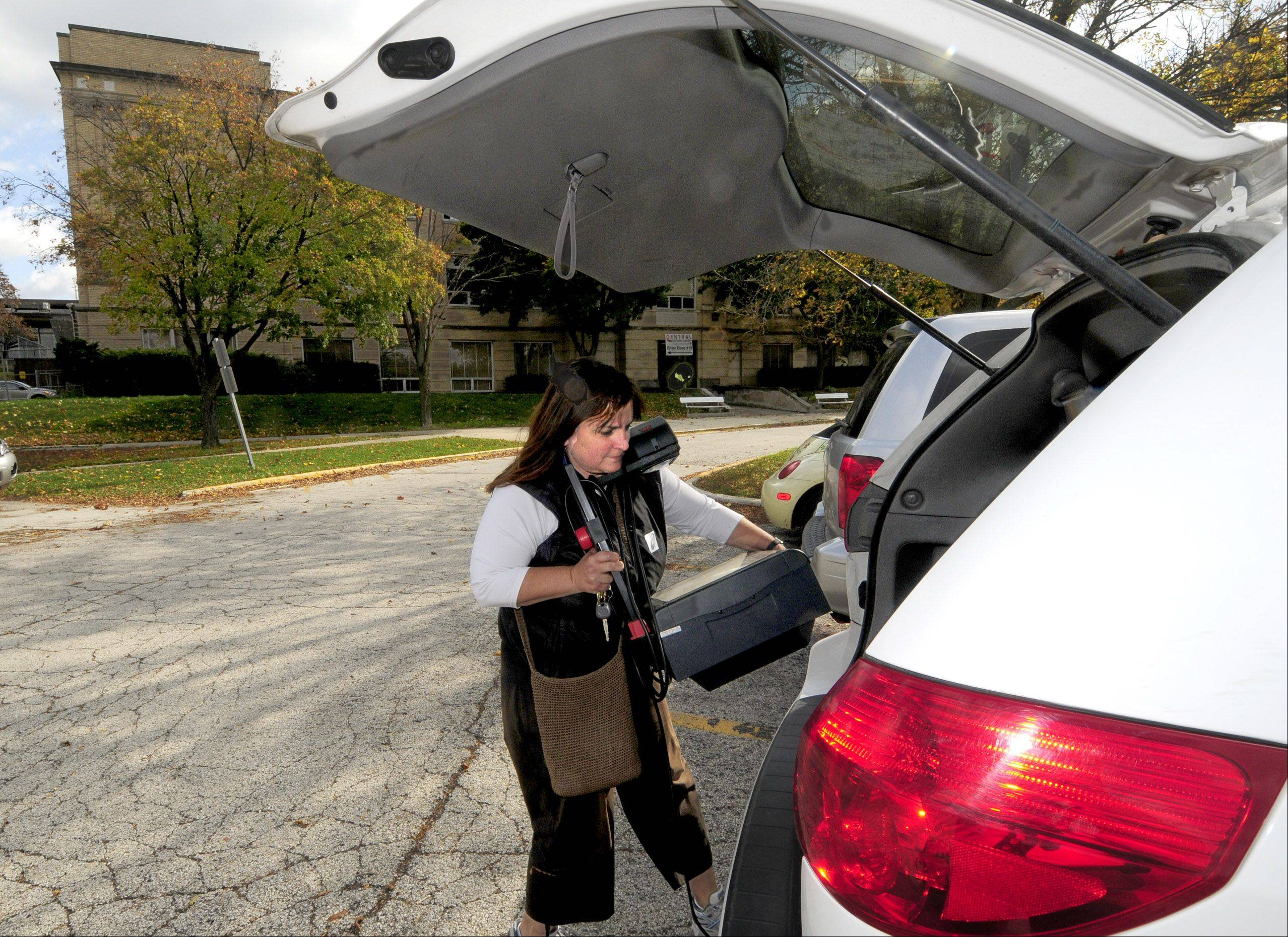 After plugging it in to make sure it works, Cindy Spivey loads an overhead projector into her car.