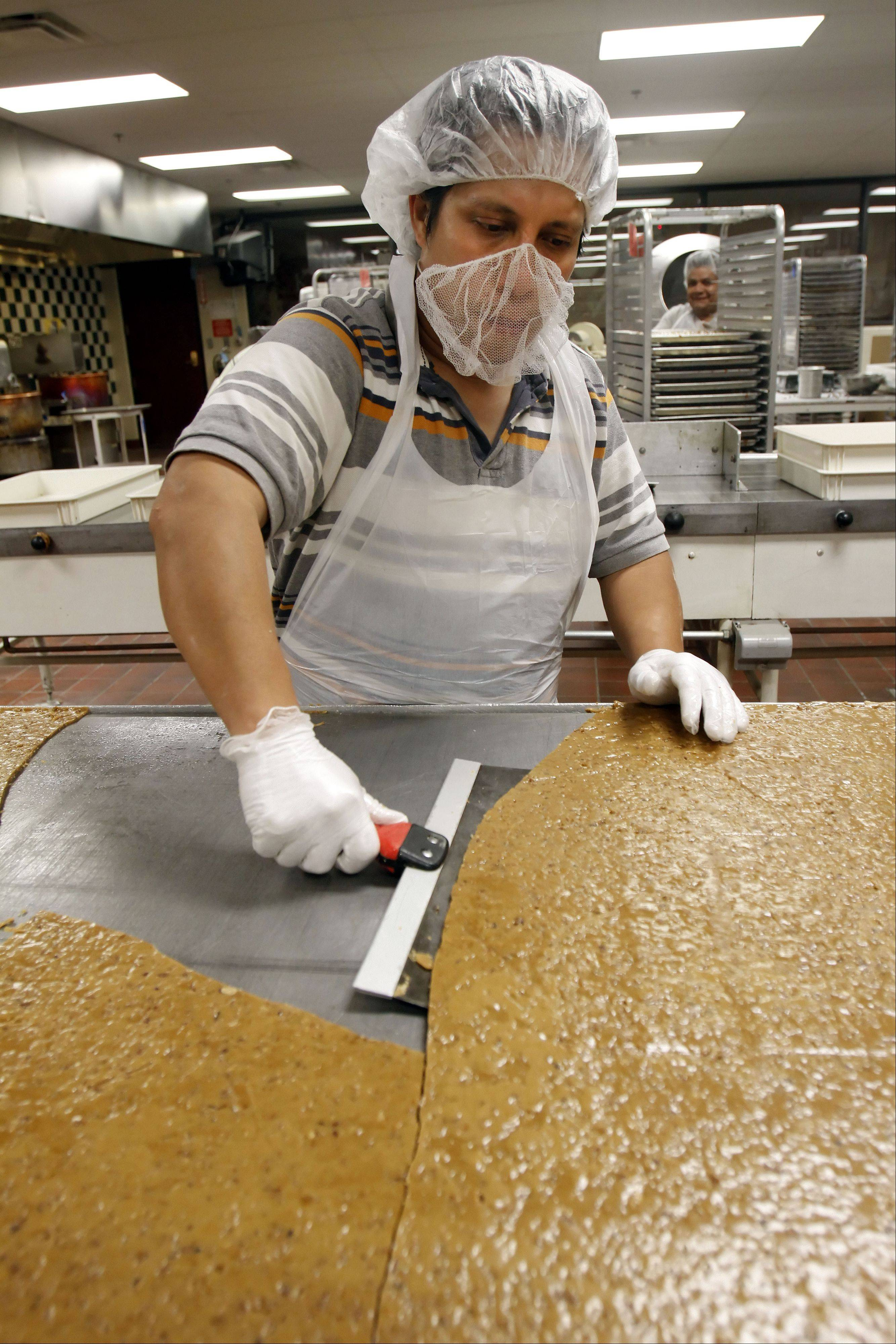 Isaias Gil breaks a huge sheet of toffee with a spatula at Long Grove Confectionery's production facility in Buffalo Grove.