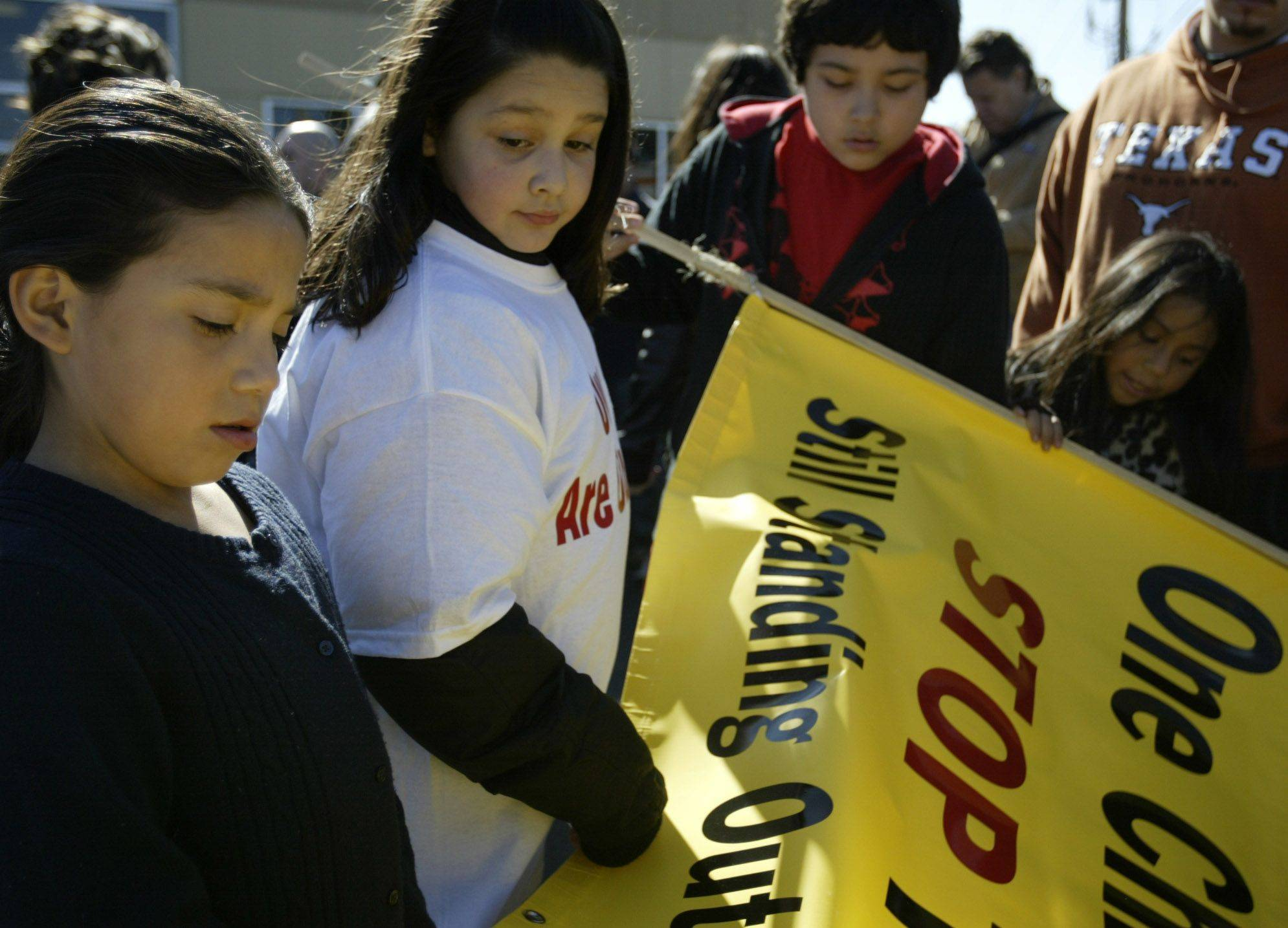 Alma Rosiles, left, 10, of Elgin, Alexis Garza, 10, of Elgin, and Jose Bosque, 11, of Elgin look at a sign before marching to protest gang violence in honor of Eric Galarza Jr. who was recently killed. More than 100 people marched with signs and shirts protesting the violence.