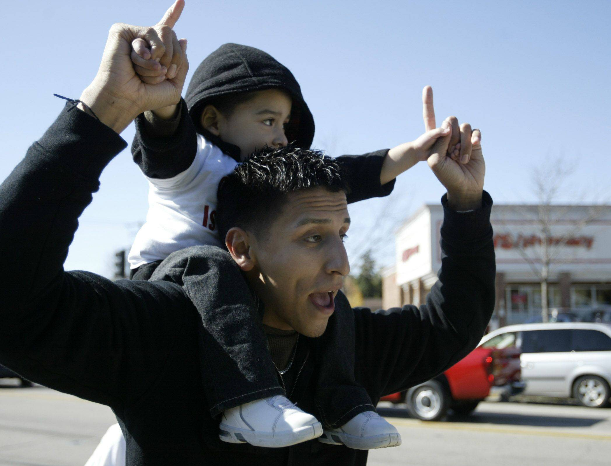 Jose Montoya of Elgin holds Xavier Sanchez, 3, of Elgin, on his shoulders during a Saturday march to protest gang violence in honor of Eric Galarza Jr. who was recently killed. More than 100 people marched with signs and shirts protesting the violence.