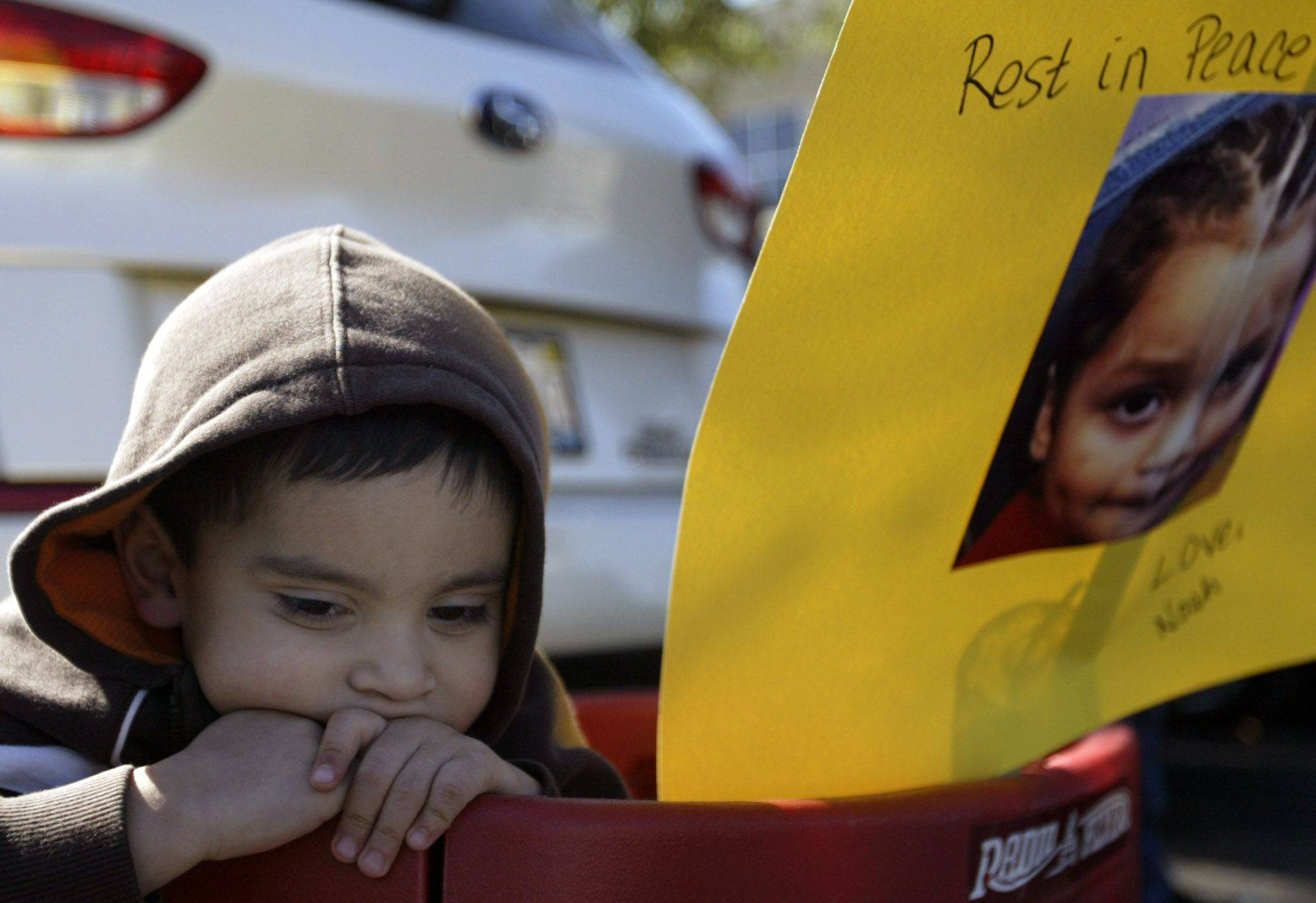 "Noah Arreguin, 4, of Elgin, sits in a wagon before marching to protest gang violence in honor of Eric Galarza Jr. who was recently killed. The Arreguin family are friends with the Galarza family. ""We should stop this violence, no one should die that way,"" 11-year-old Delaney Arreguin said."