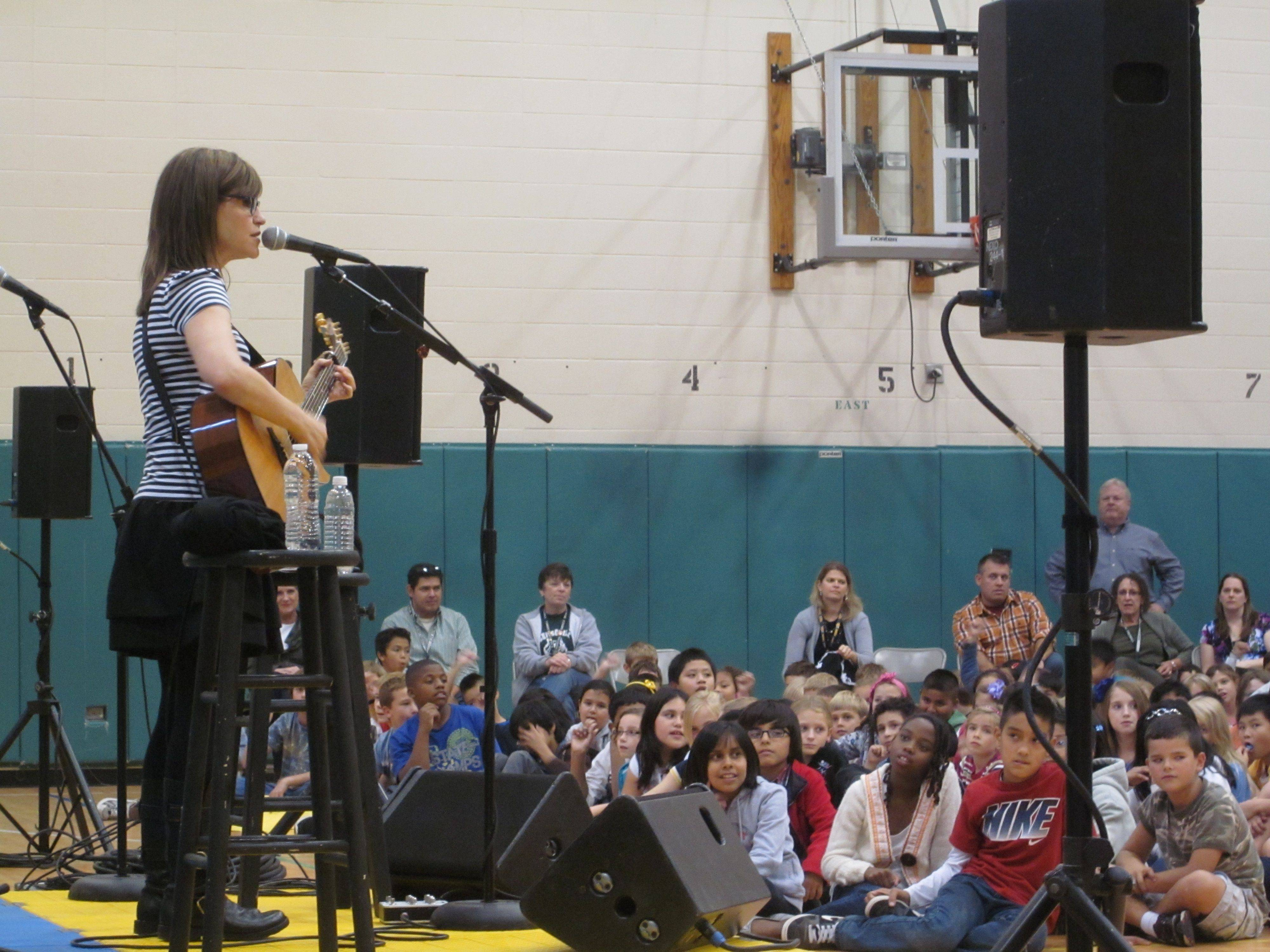 "Students and teachers at Churchill School in Glen Ellyn listen Friday afternoon to Lisa Loeb perform songs from her book ""Lisa Loeb's Silly Sing-Along: The Disappointing Pancake and Other Zany Songs."""
