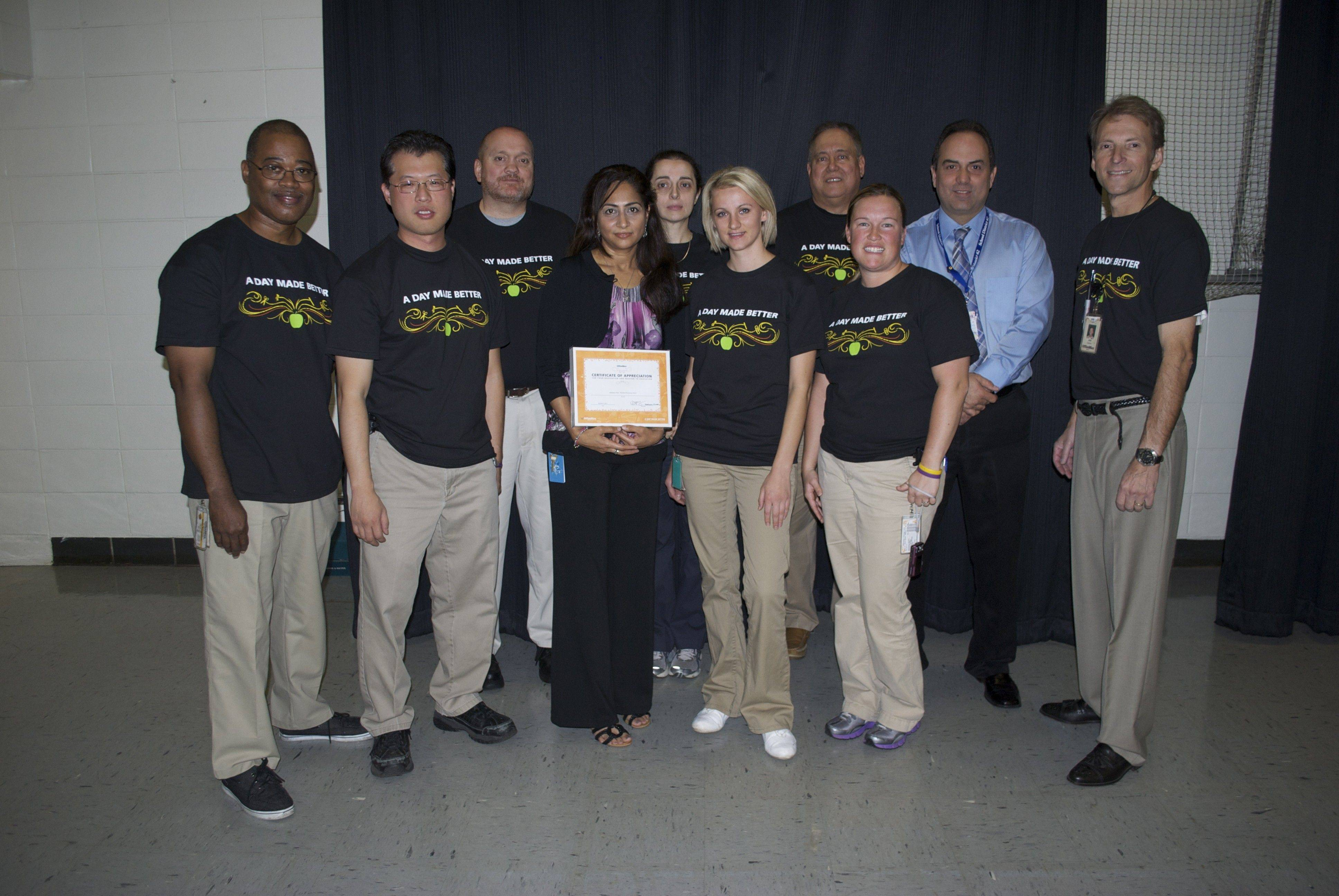 "OfficeMax representatives surprised Plainfield teacher, Mahjabeen Patel, with $1,000 in school supplies and a certificate as part of ""A Day Made Better"" National School Advocacy Program. Pictured, from left: Front row: Dale Ferguson, James Nicholson, honoree Mahjabeen Patel, Barbara Kanoza, Kelly Redican and Jim Delaney; back row: Chris Flaschberger, Ursula Kubowicz, Kirk Gautreau and Plainfield Principal Ray Ruiz."