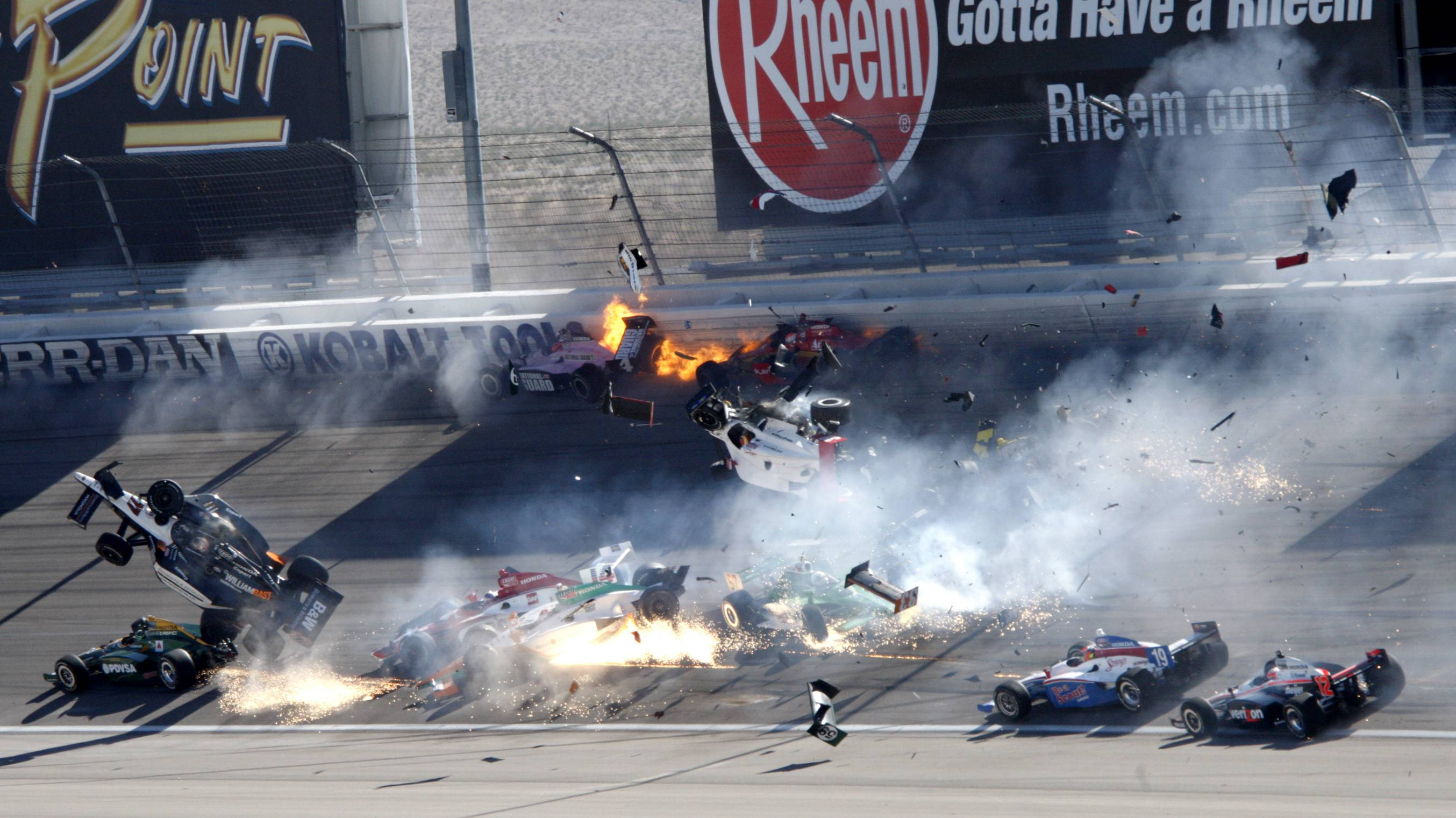 Drivers, including Dan Wheldon (77, in air at left), crash during a wreck Sunday that involved 15 cars during the IndyCar Series' auto race at Las Vegas Motor Speedway in Las Vegas.