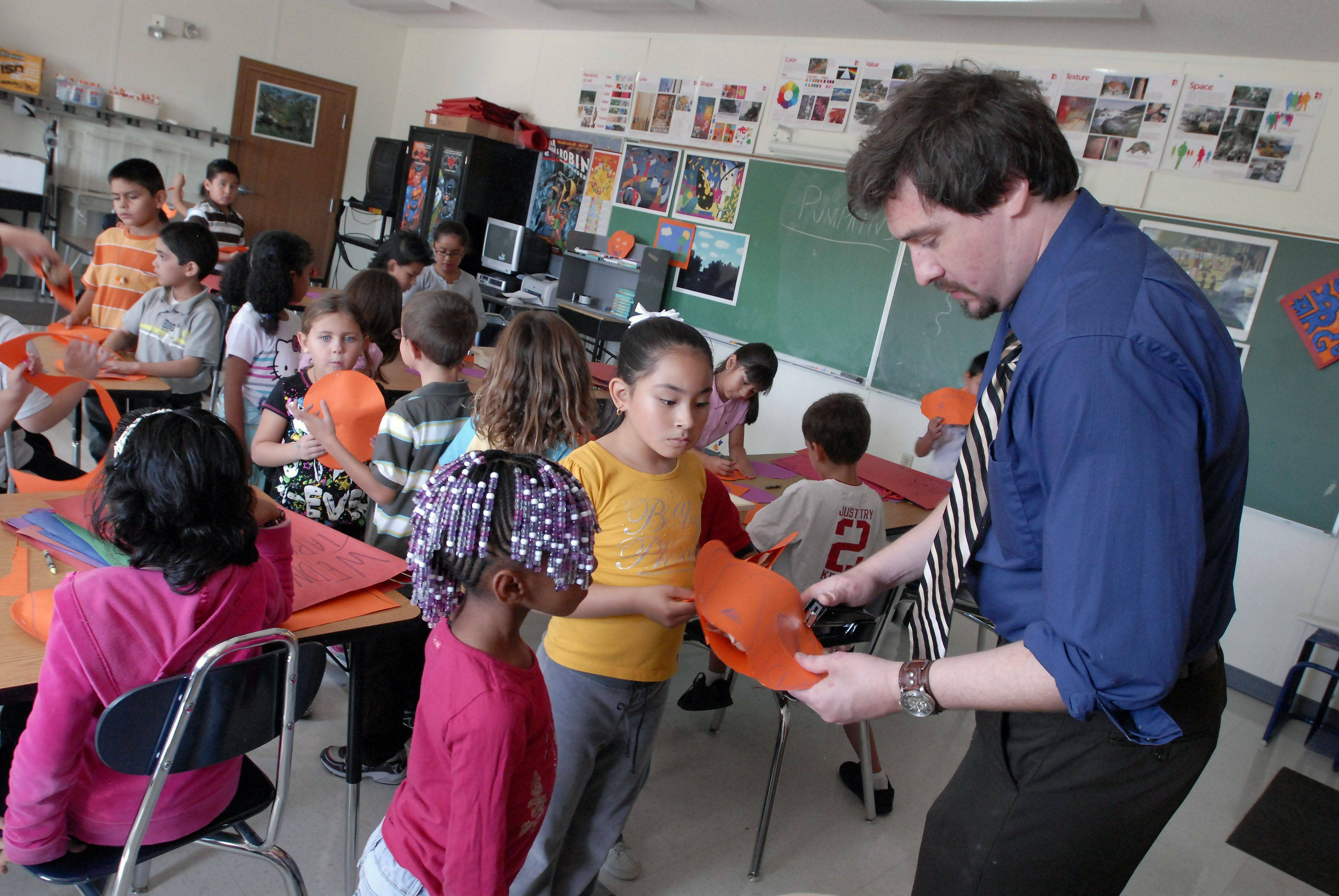 Students vie for attention from art teacher Tom Graholski at Lincoln Elementary School in Hoffman Estates. The school is part of Elgin Area School District U-46, where school officials have been forced to make up for millions of dollars owed by the state.