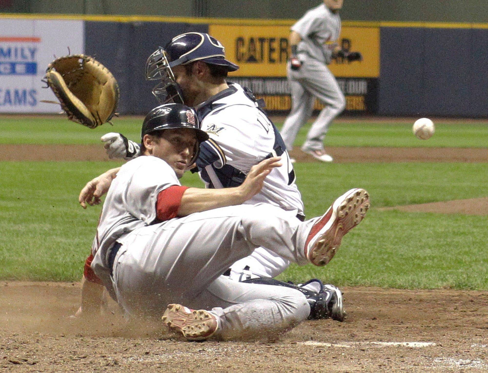 The Cardinals' David Freese knocks the glove and ball away from Milwaukee Brewers catcher Jonathan Lucroy as he scores on a sacrifice fly by Adron Chambers during the fifth inning Sunday.