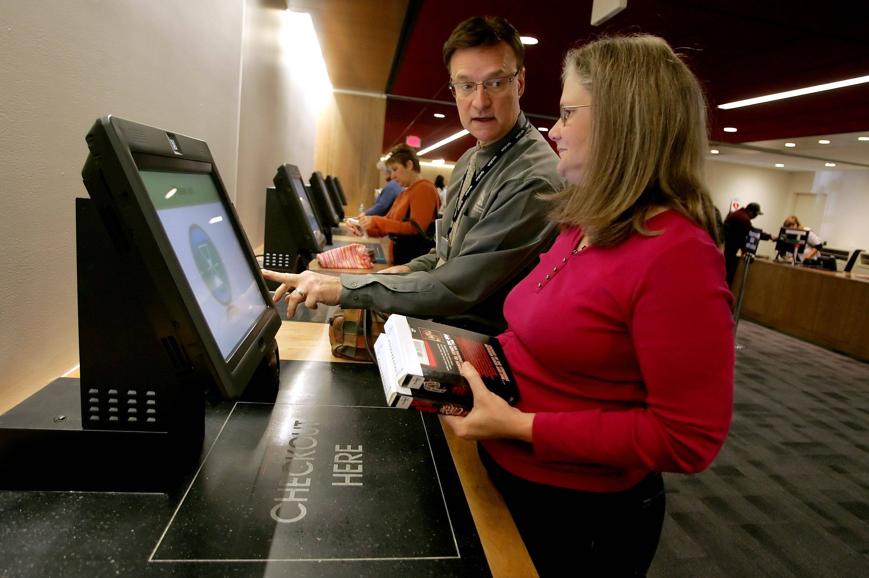 Warren-Newport Public Library Director Stephen Bero, center, helps Kate Ausdenmoore of Gurnee with the new XpressCheck checkout system Monday on the first day of library's reopening in Gurnee. The library has been closed since Sept. 12 due to construction additions and remodeling.