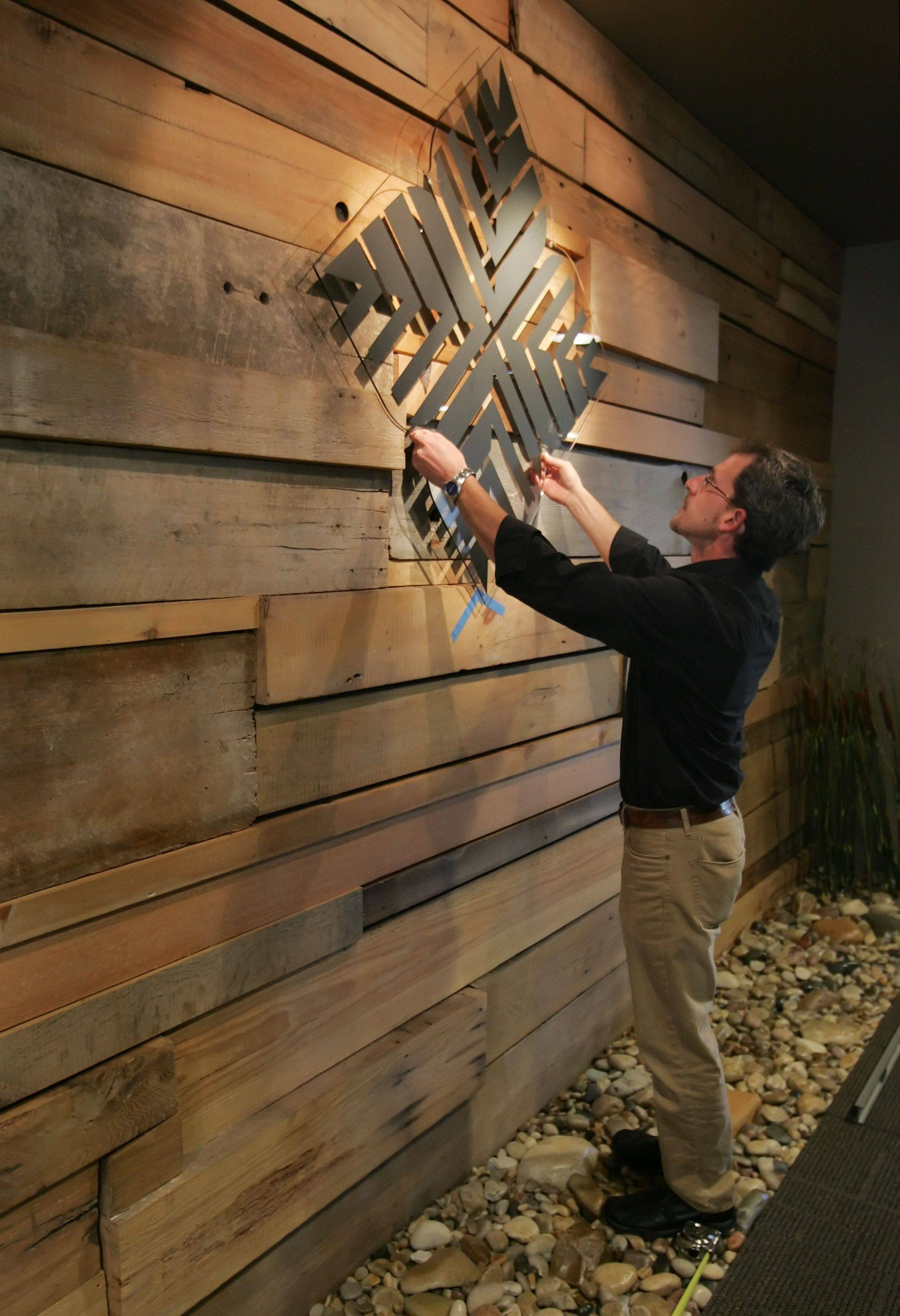 Exhibits manager Steve Furnett positions a logo on a mosaic at the new Lake County Forest Preserve District headquarters in Libertyville. Features such as the recycled wood are being used to soften the look of the former corporate office.