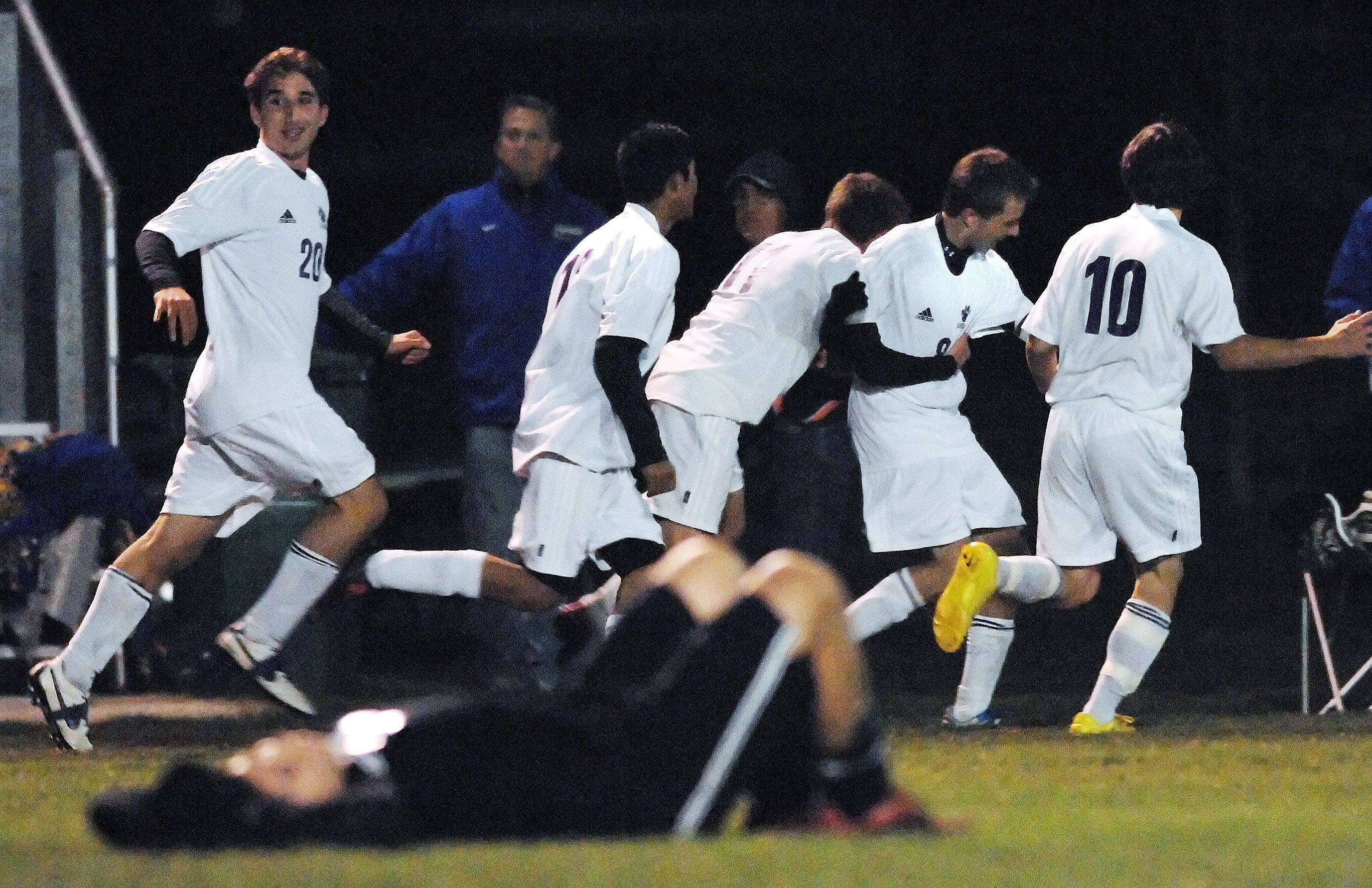 As a Prairie Ridge player lays on the field in defeat, Hampshire captain Jason Bishop is surrounded by teammates after he scored the winning goal with eight seconds left in overtime in the Hampshire regional game Tuesday.