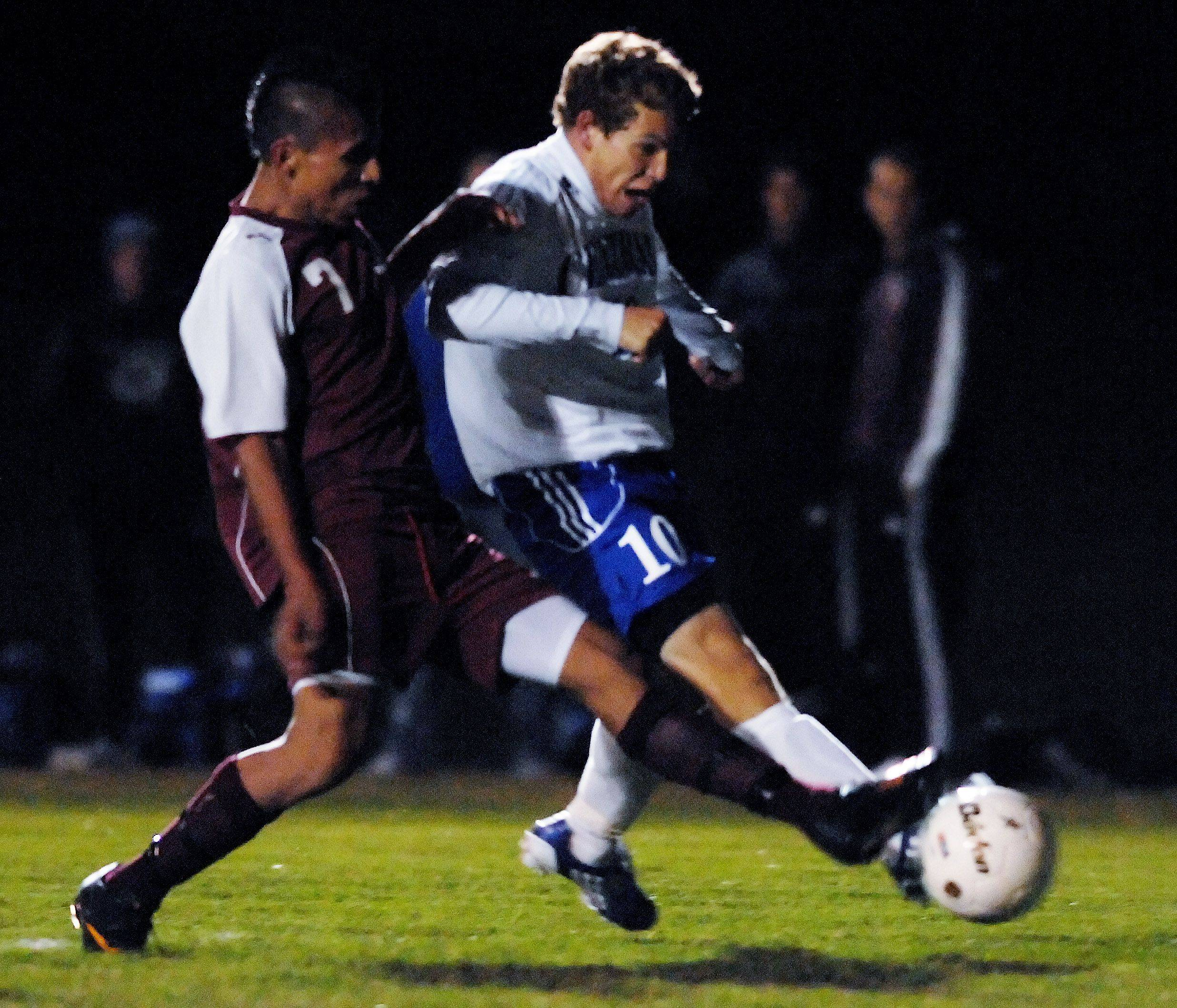 Burlington Central's Chris Gousios gets a shot off as Marengo's Frolan Matinez tries to stop him in the Hampshire regional game Tuesday. The ball rolled into the net for Gousios' third goal of the night, and the Rockets won 3-0.