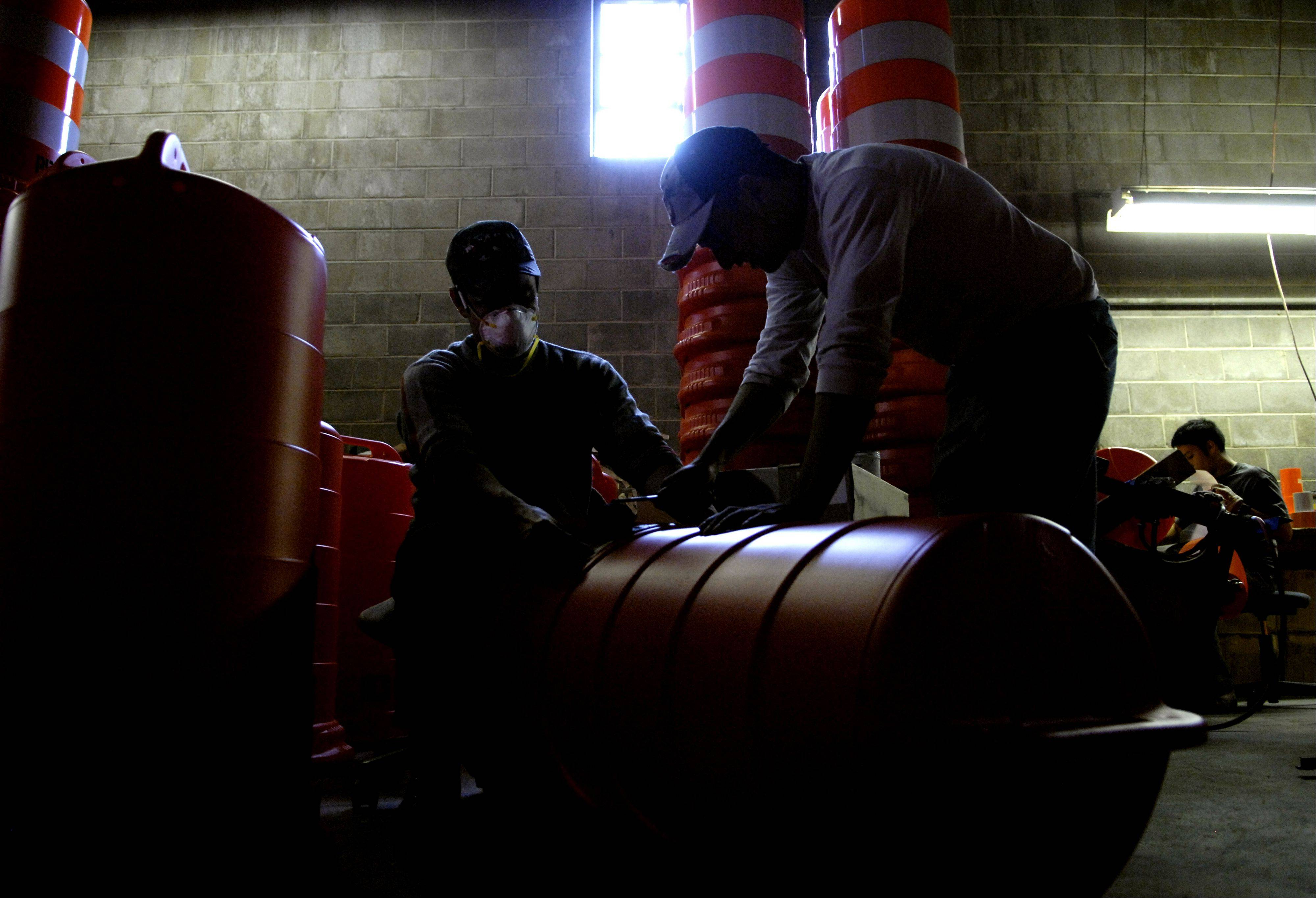 Barrels are labeled for a customer with a stencil at Work Area Protection Corp. in St. Charles Wednesday.