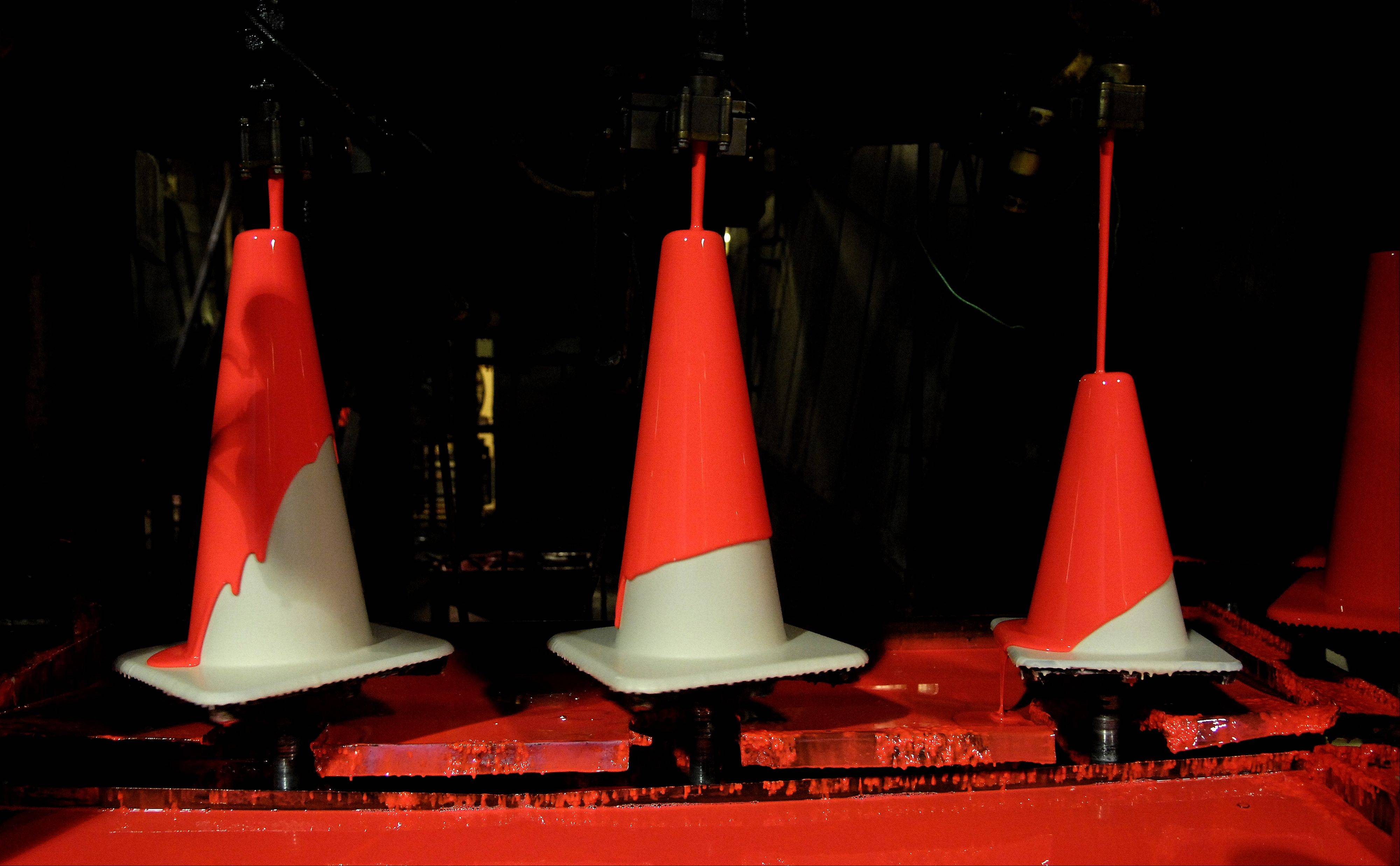 Cones start black, then are painted white before the orange plastic layer is poured over them.