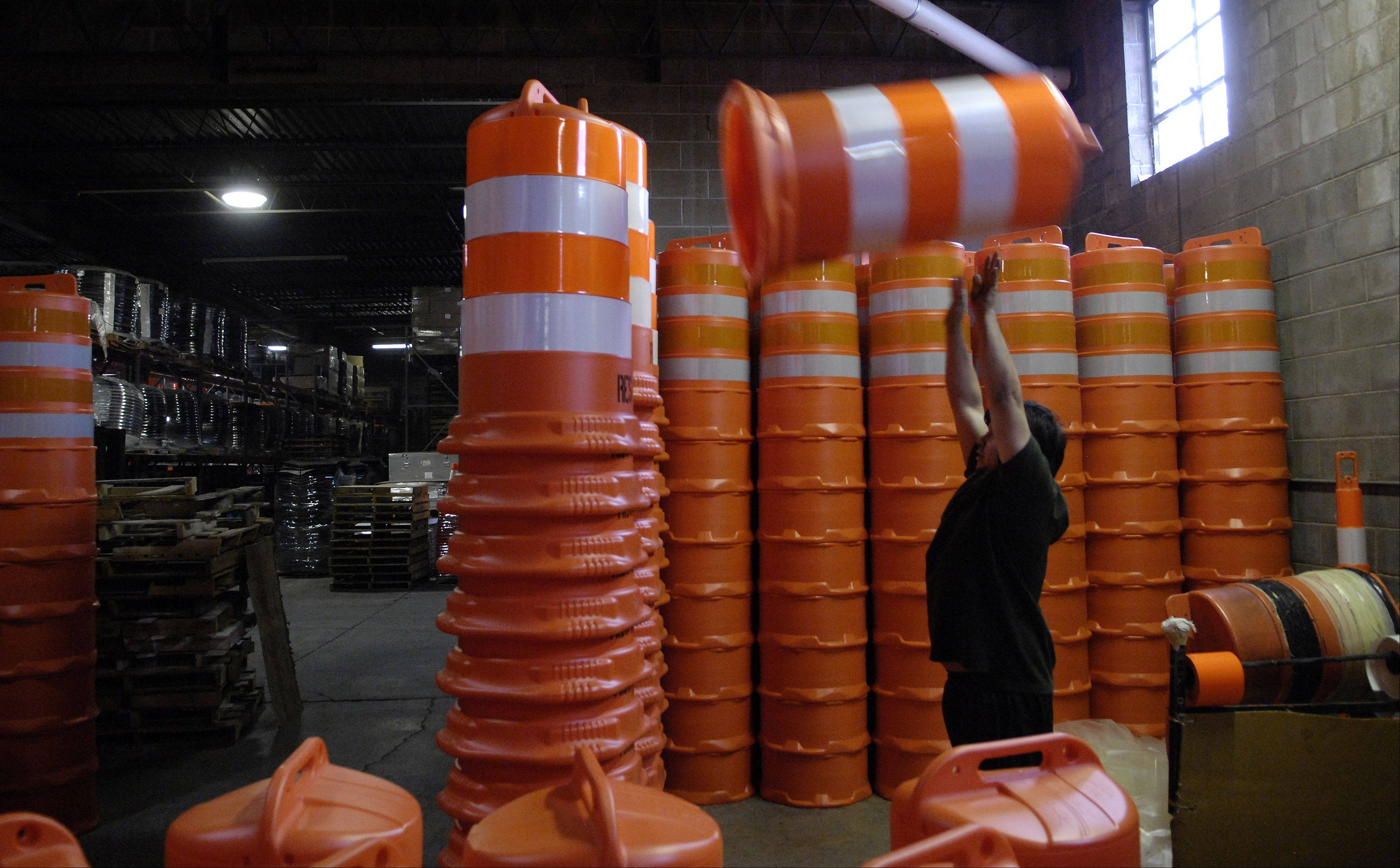 Victor Mendoza tosses a barrel onto a stack after wrapping it in reflective tape.