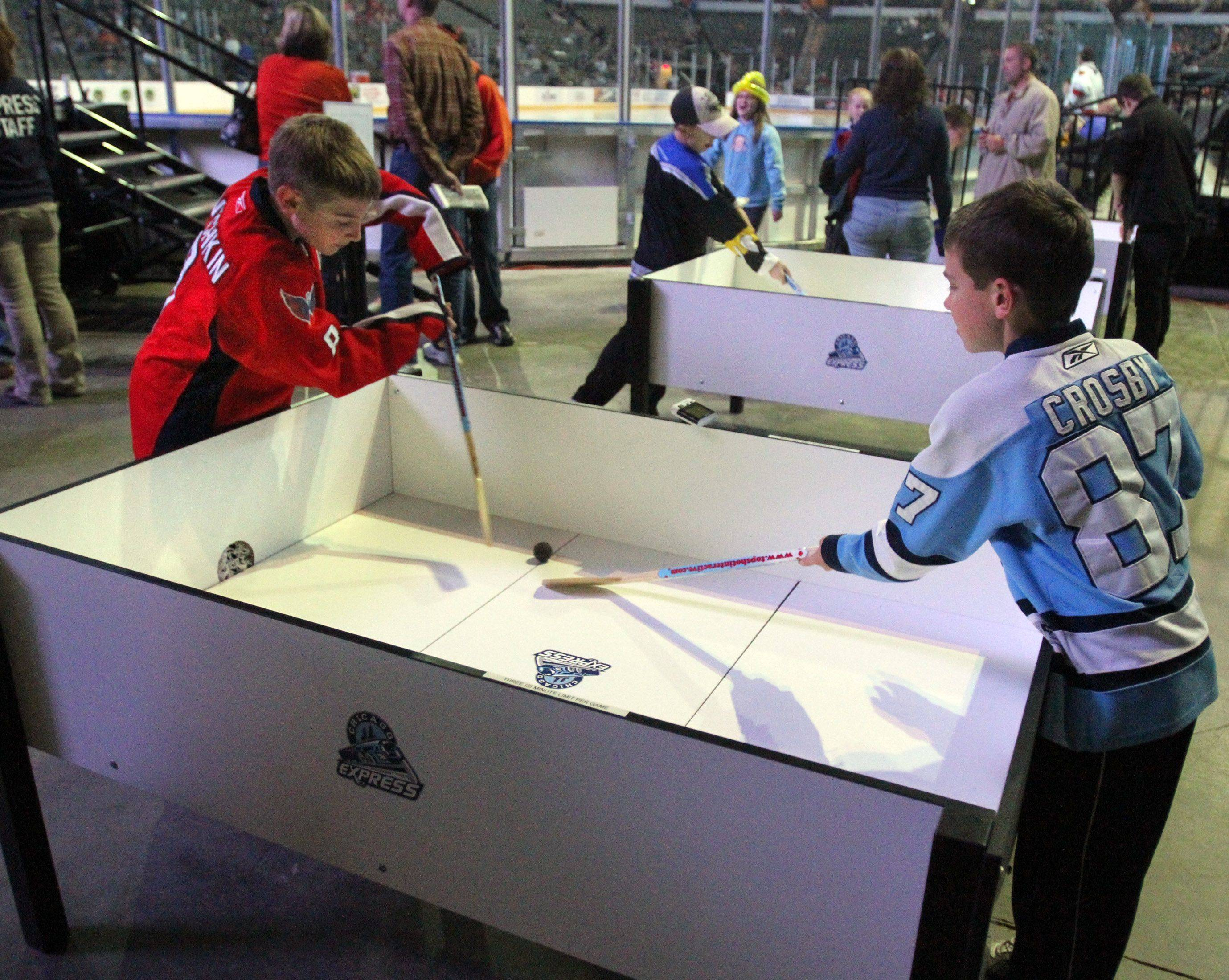 Ian McKittrick, 10, left, and his brother Cal, 8, of Geneva play one of many types of hockey games for kids at Chicago Express home opener in Hoffman Estates on Saturday, October 22nd.