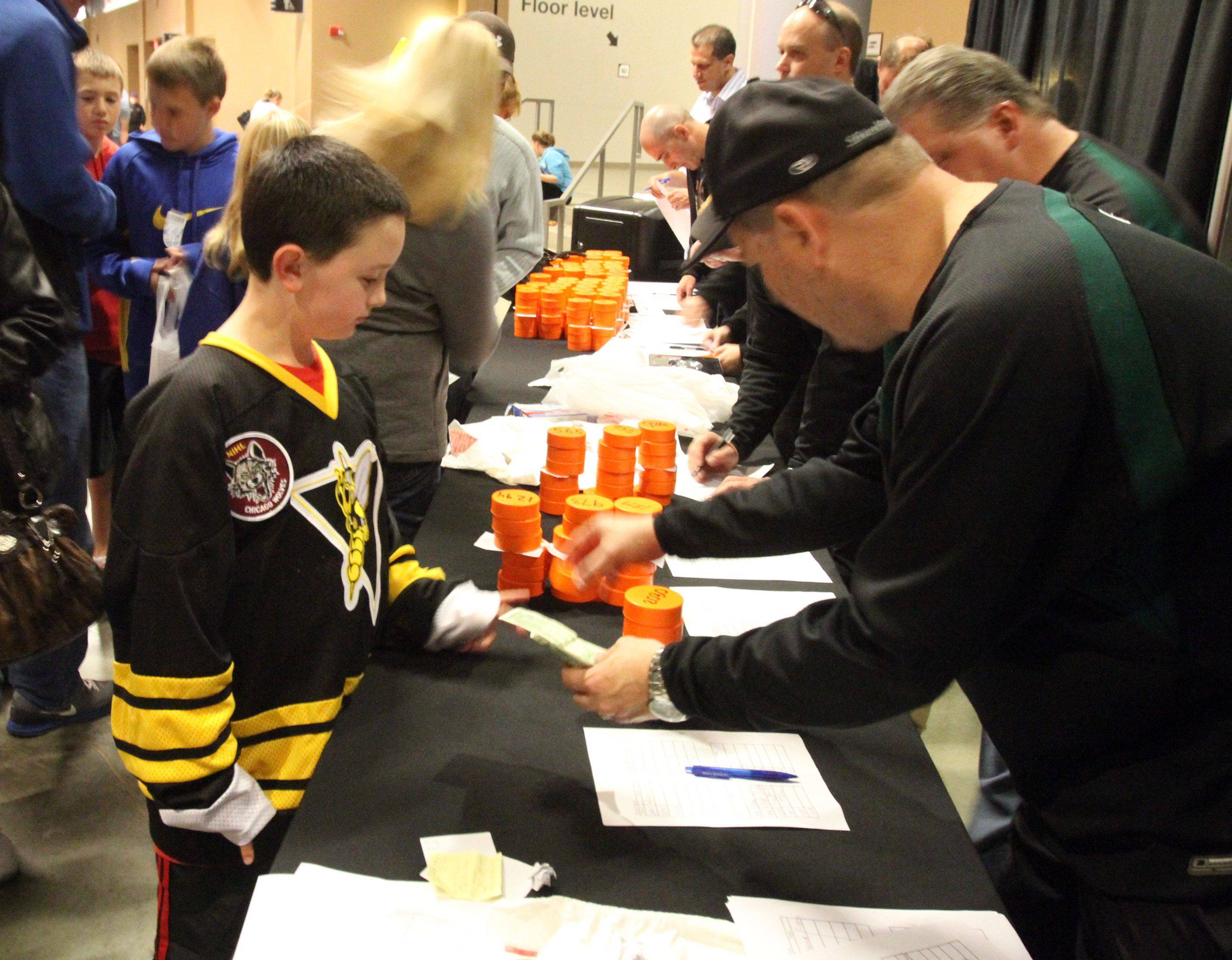 Joshua Pavelko, 8, of Crystal Lake, signs up for the chuck-a-puck before the Chicago Express home opener Hoffman Estates on Saturday, October 22nd.