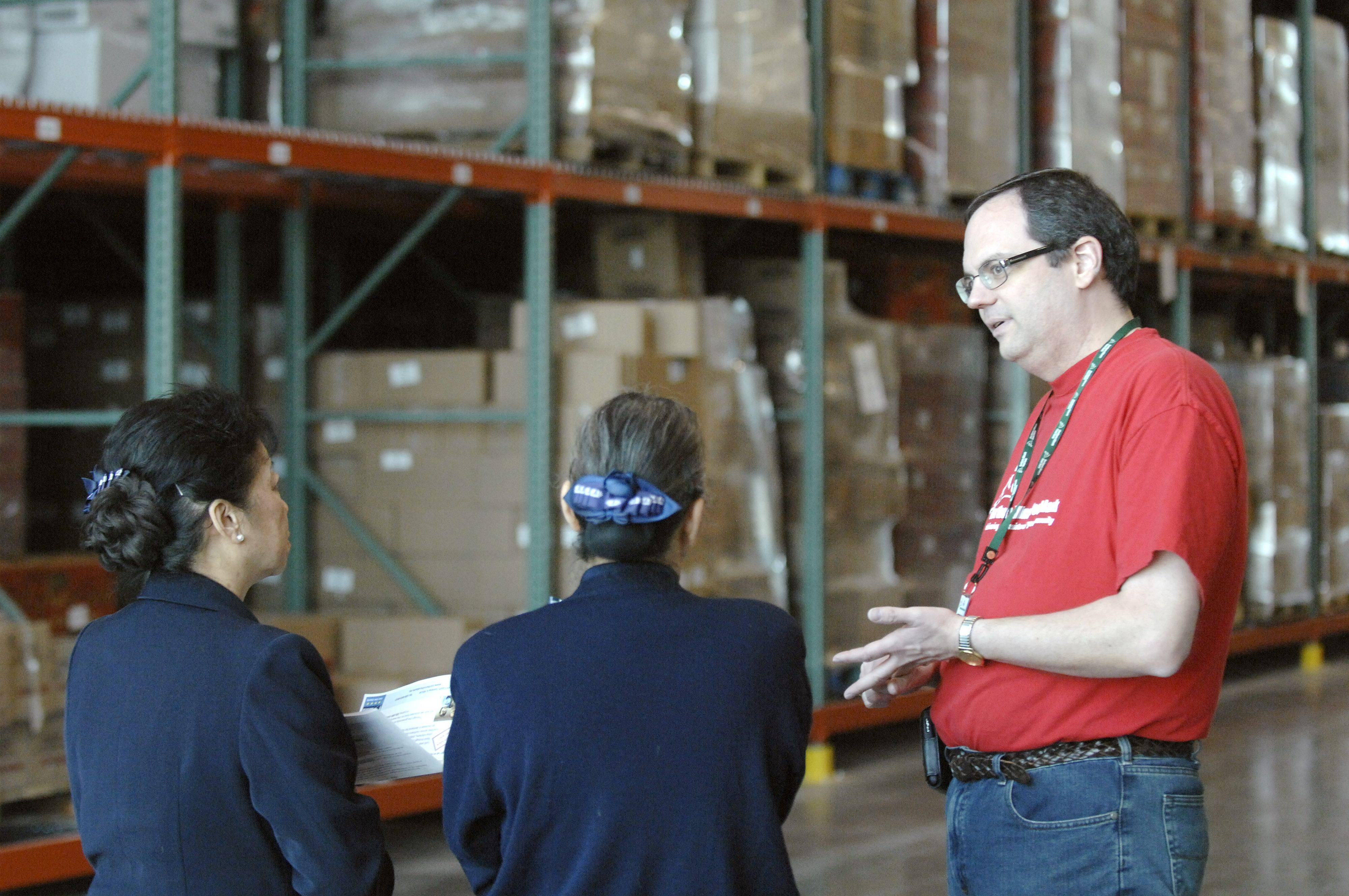 Volunteer supervisor Scott Heinzman talks to Pin Hwang, left, and Emilie Chain of the Buddhist Tzu Chi Foundation, in Darien, on Saturday in the warehouse of the new Northern Illinois Food Bank in Geneva.