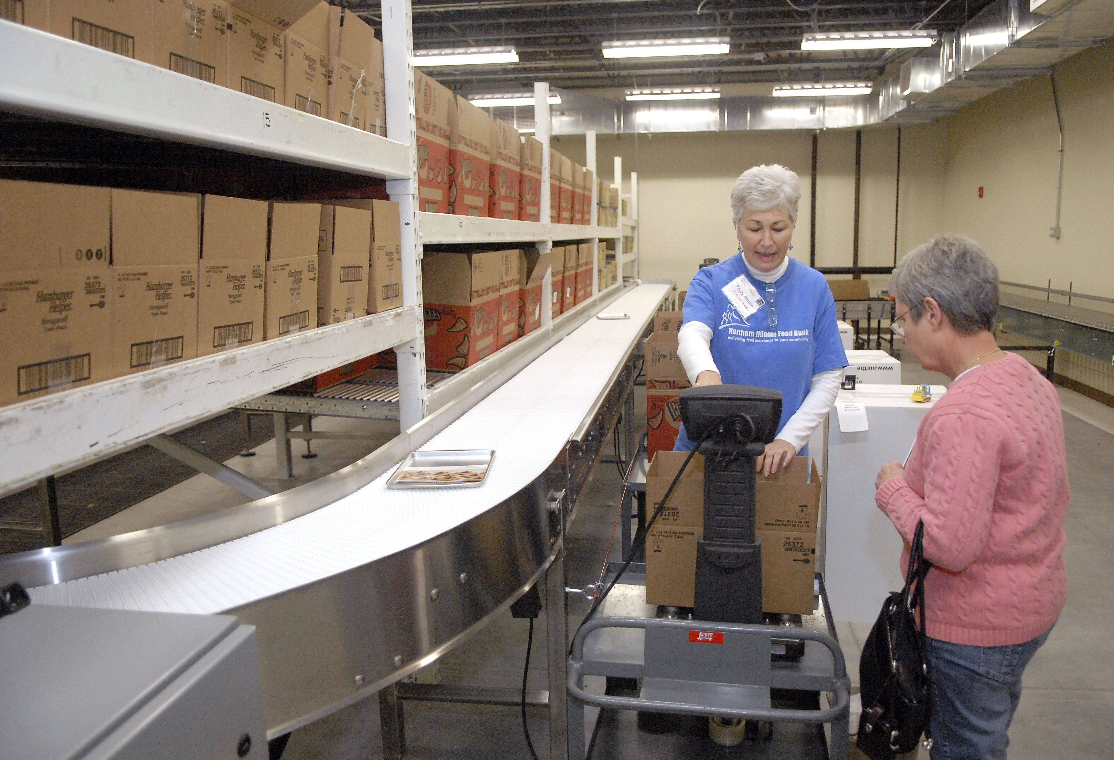 Volunteer Peggy Benzin of Carol Stream shows Mary E. Gustafson how boxes are weighed in the processing room at the new Northern Illinois Food Bank location in Geneva on Saturday.
