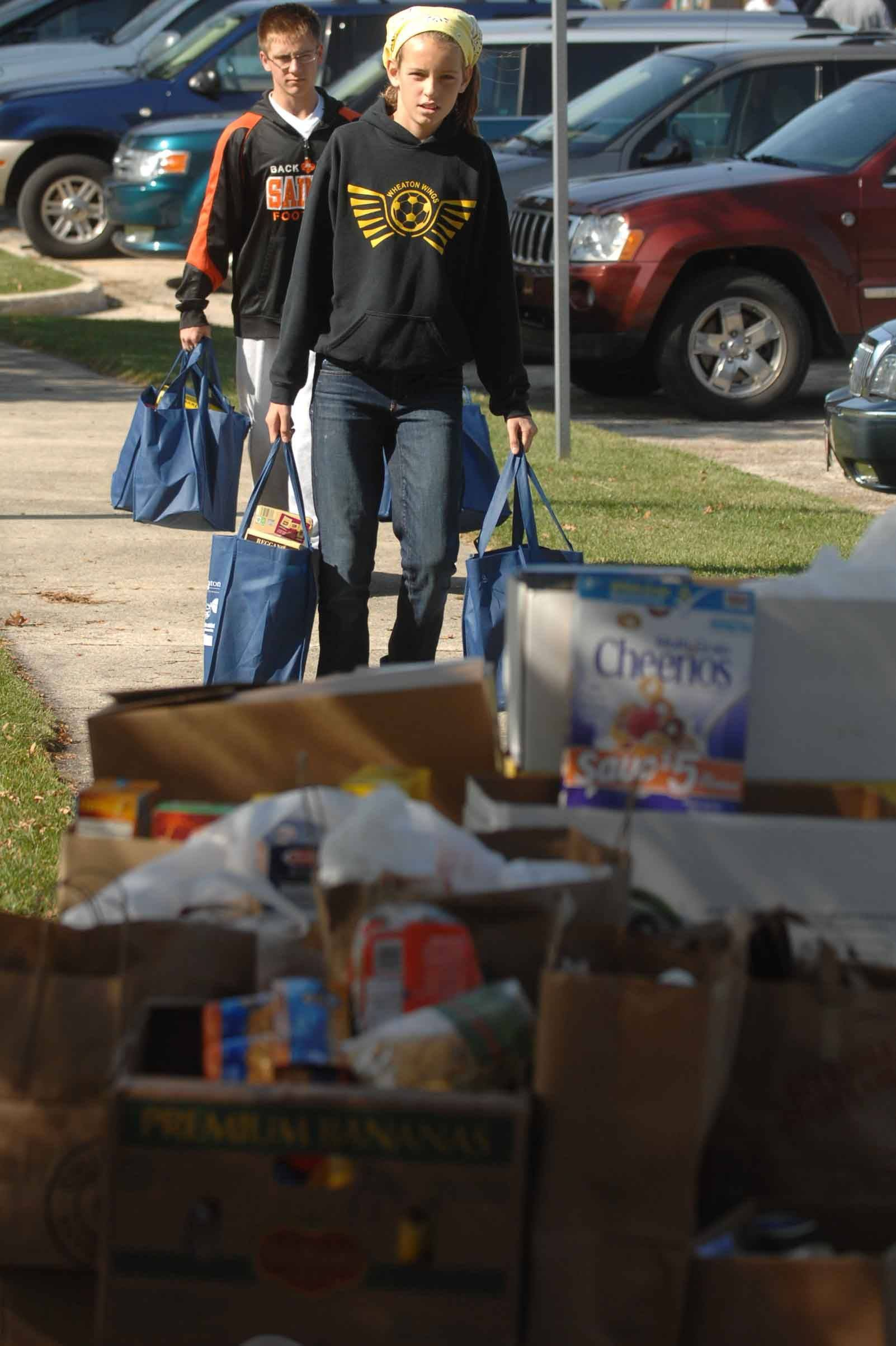 Shannon Moran, 11, carries bags of food to be donated to People's Resource Center during the Make a Difference Day Stuff a Truck with Food drive Saturday in Wheaton.