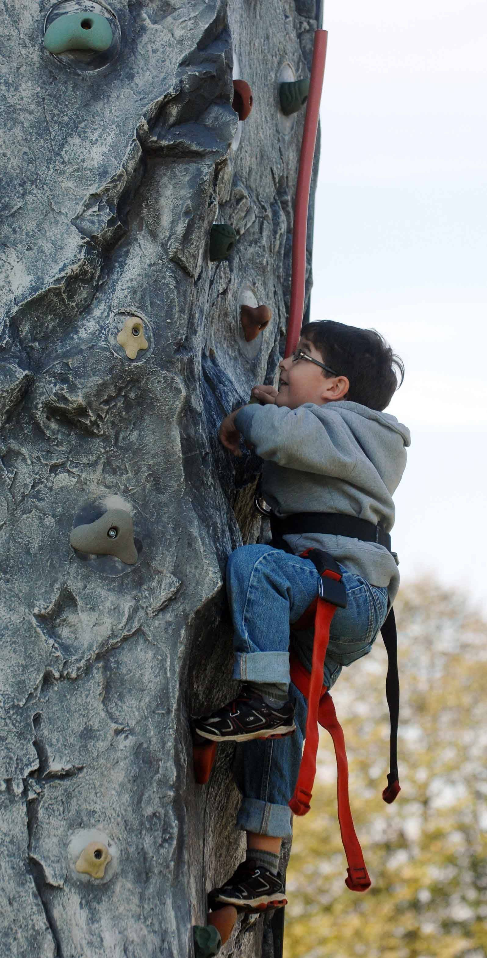 Nicholas Sanguinetti, 5, of Wheaton, climbs the rock wall Saturday during a festival held in conjunction with Make a Difference Day.