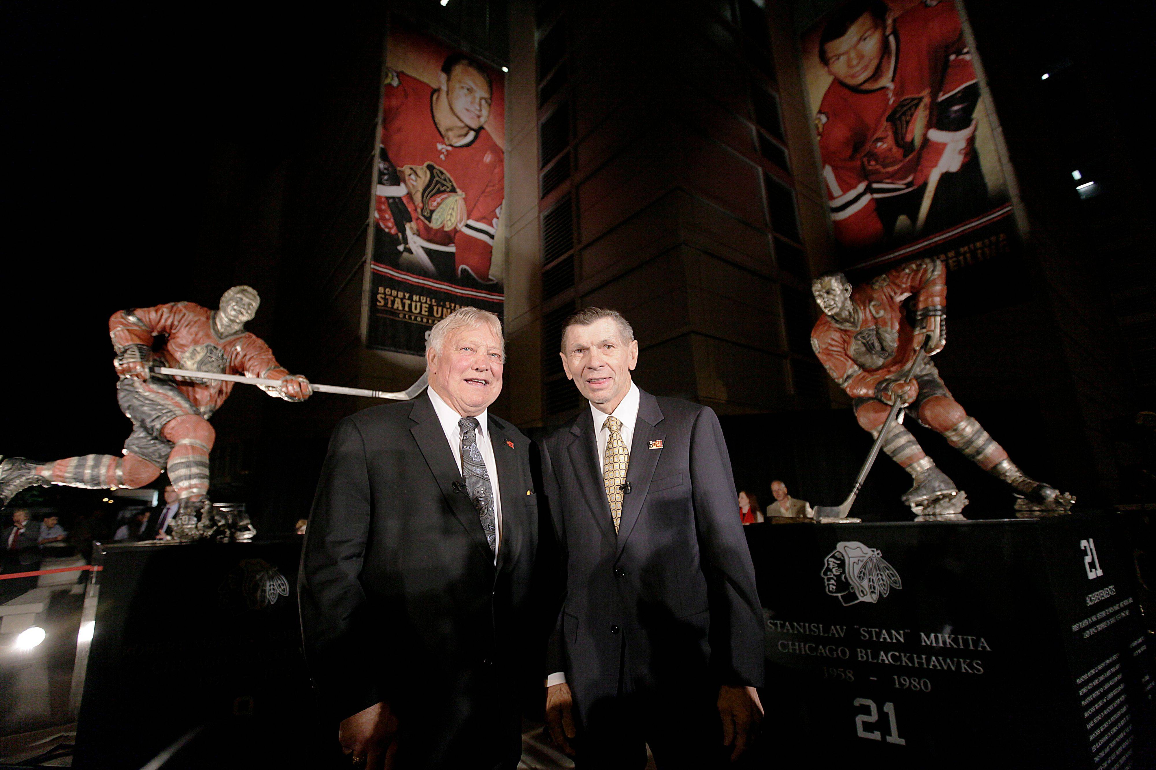 Blackhawks Hall of Famers Bobby Hull, left, and Stan Mikita stand in front of their statues after their unveiling Saturday night outside the United Center.