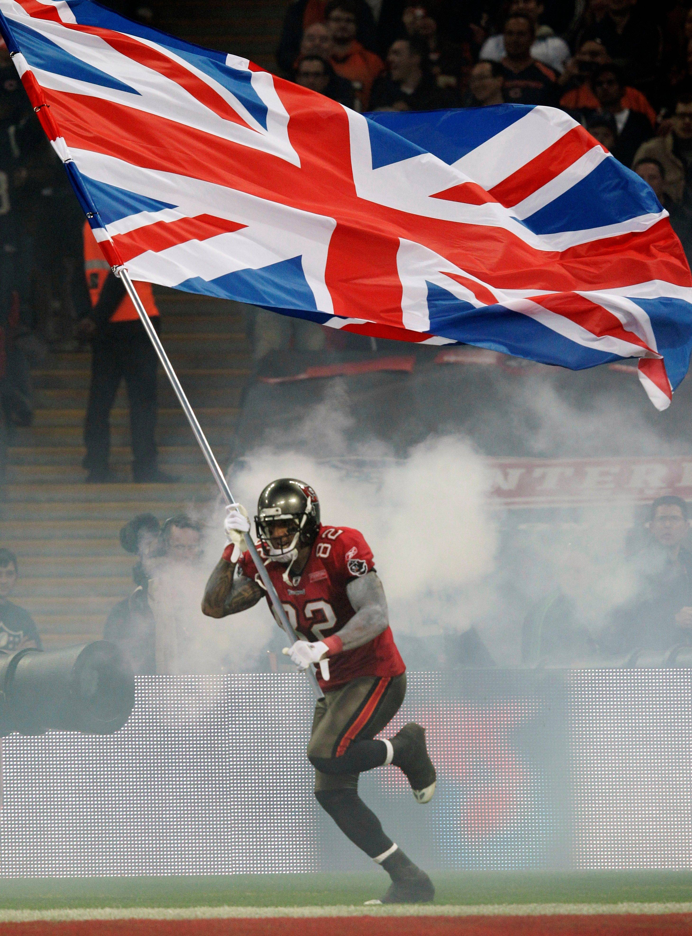 Tampa Bay Buccaneers tight end Kellen Winslow carries a British flag onto the field before an NFL football game against the Chicago Bears at Wembley Stadium in London.