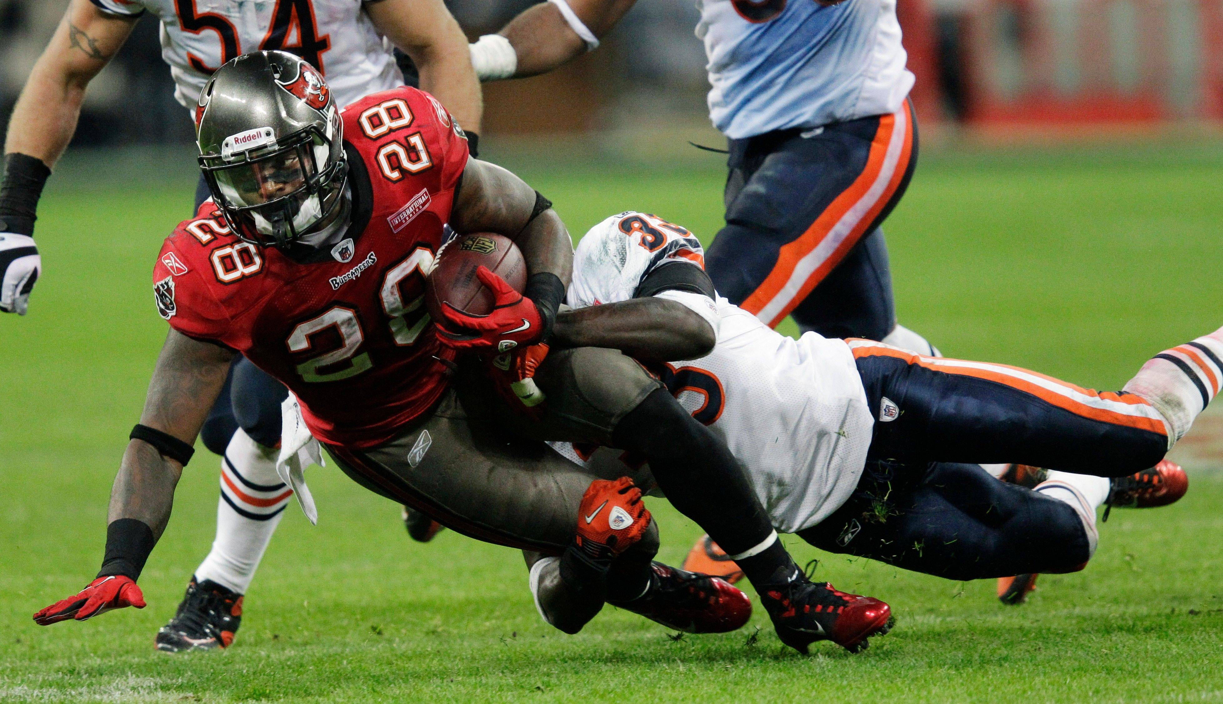 Tampa Bay Buccaneers running back Kregg Lumpkin is taken down by Chicago Bears cornerback Charles Tillman during the second half.