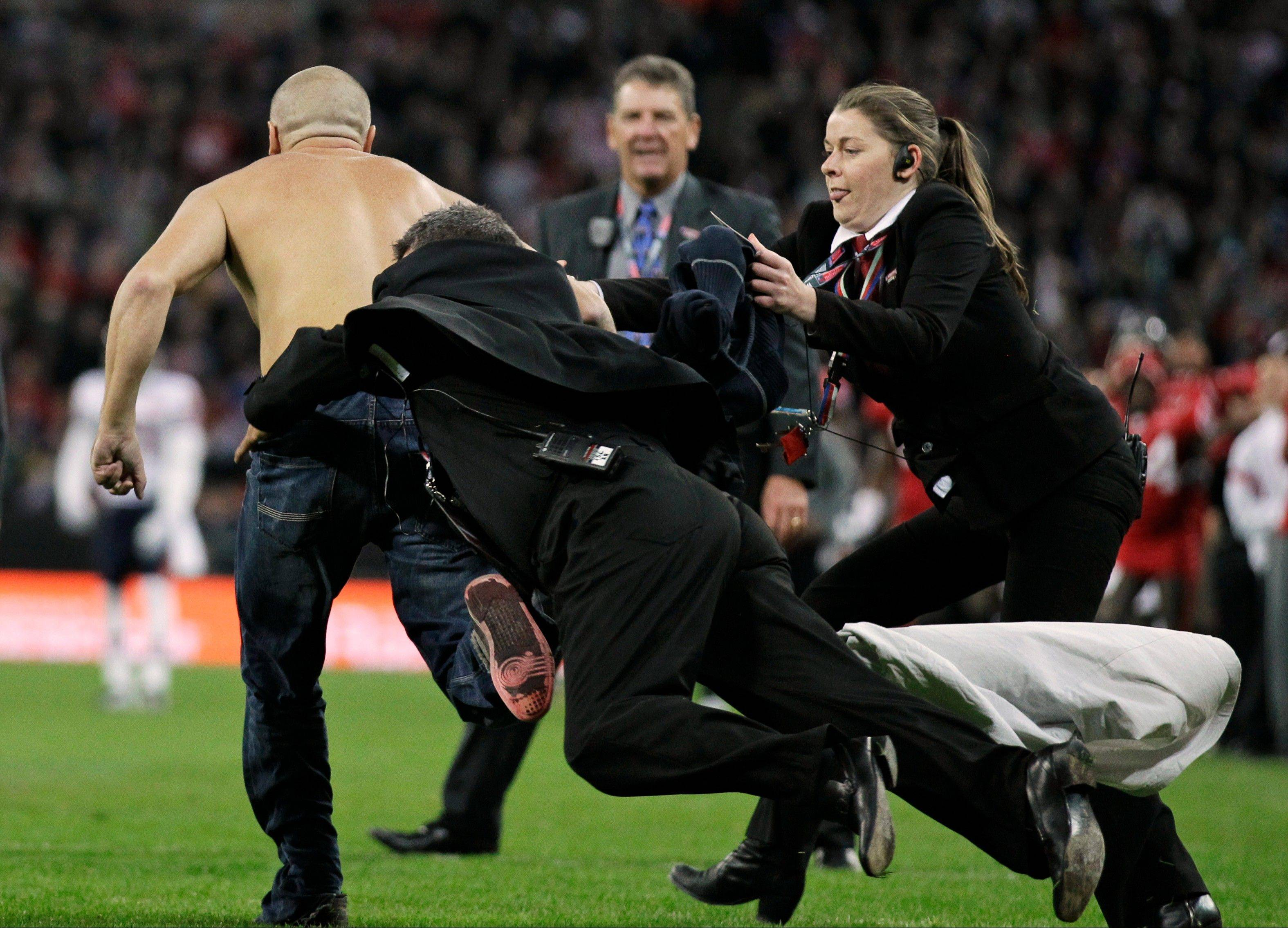 Security officers tackles a fan as he runs on to the field during the second half of an NFL football game between the Tampa Bay Buccaneers and Chicago Bears at Wembley Stadium in London.