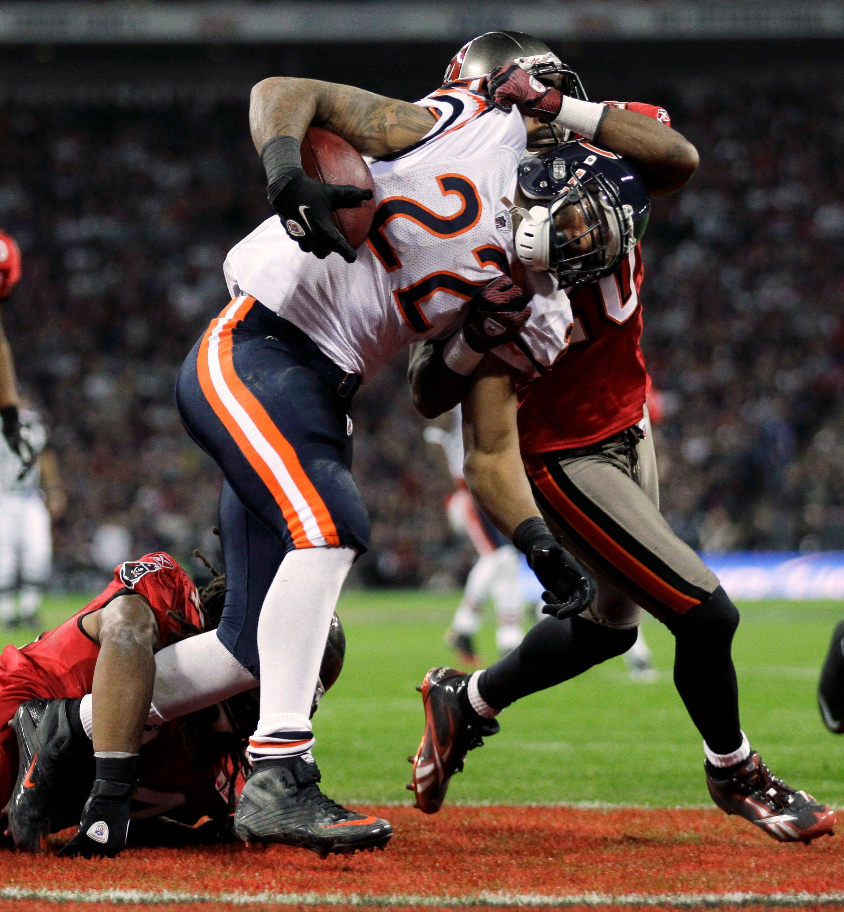 Chicago Bears running back Matt Forte is taken down by Tampa Bay Buccaneers cornerback Ronde Barber and Adrian Clayborn, left, in the Buccaneers' end zone for a safety during the first half.