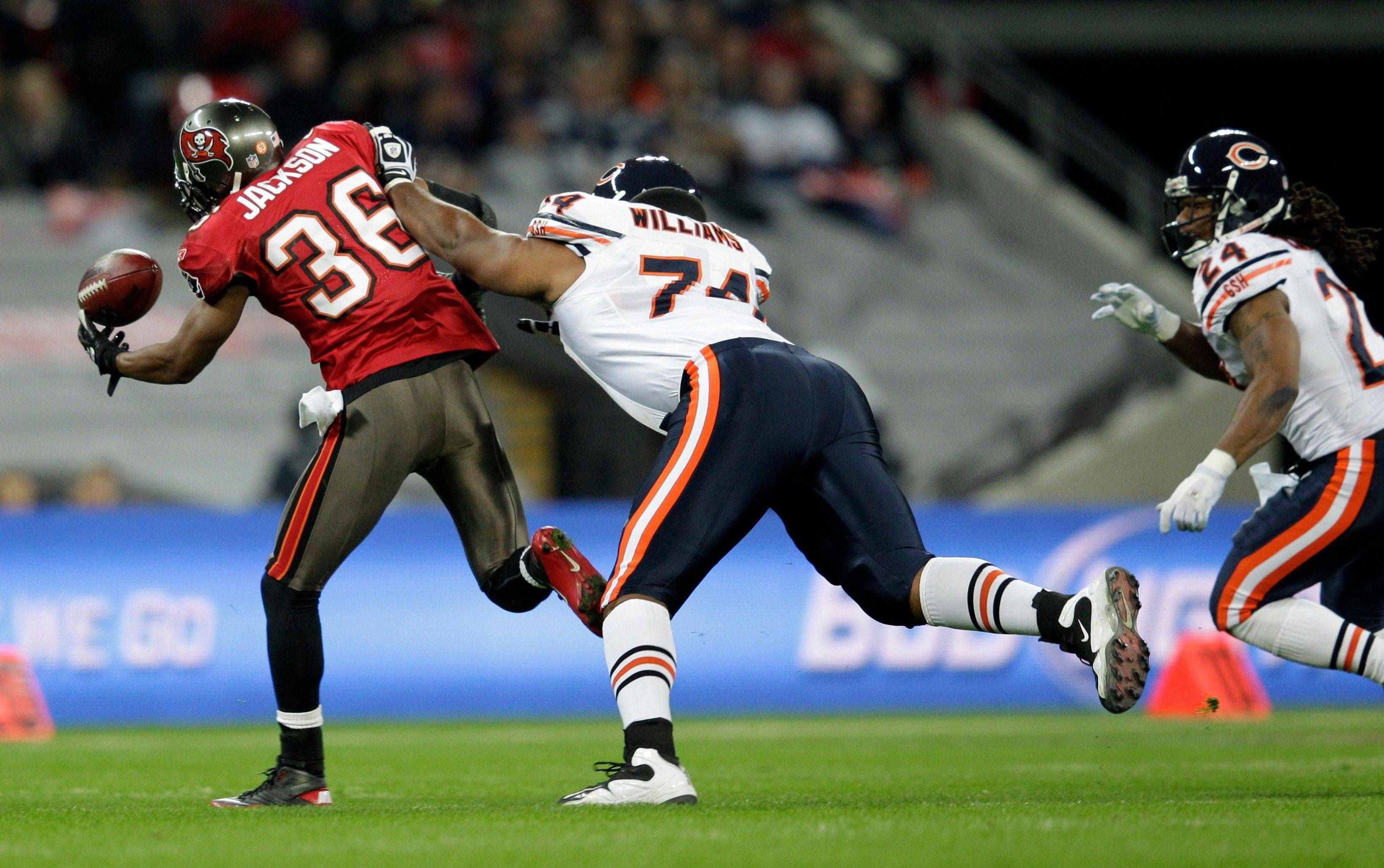 Chicago Bears guard Chris Williams tries to stop Tampa Bay Buccaneers defensive back Tanard Jackson as he intercepts a pass intended for Chicago Bears running back Marion Barber, right, during the first half.