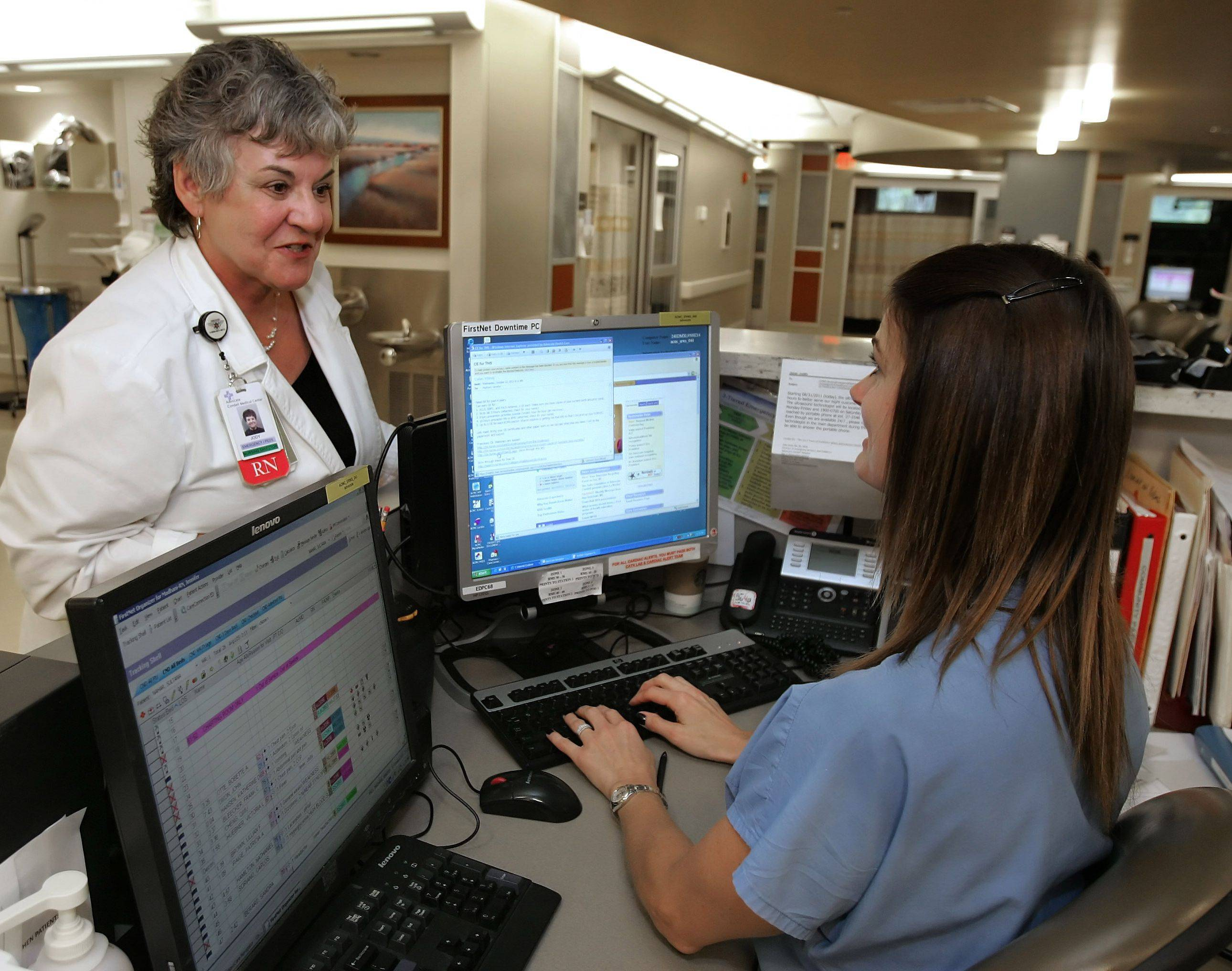 Jody Jesse, director of emergency nursing at Advocate Condell Medical Center in Libertyville, talks to registered nurse Jennifer Madhani in the hospital's emergency department.