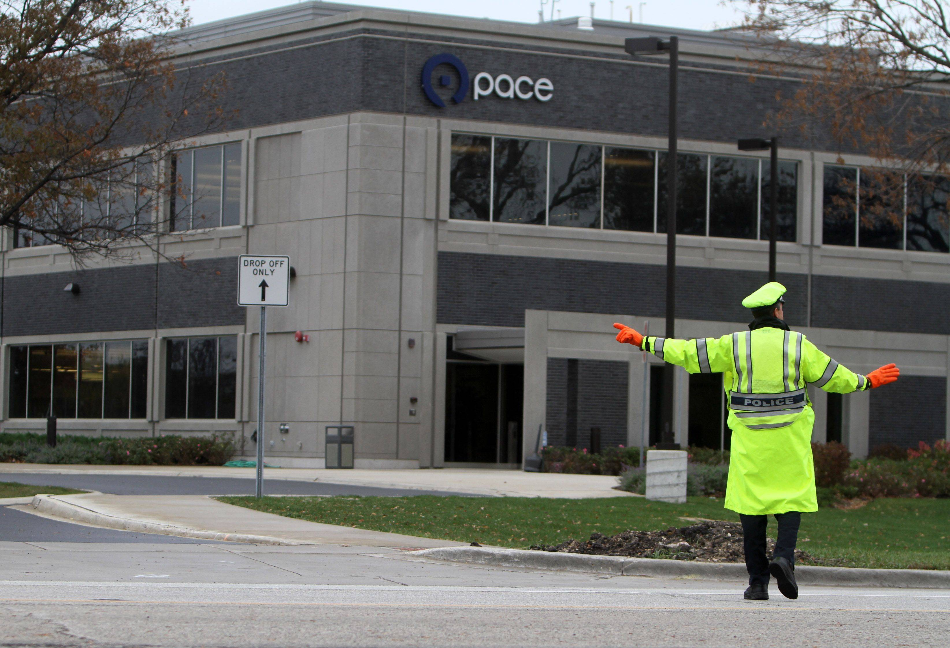 "A police officer stops traffic on Algonquin Road so cars can exit the parking lot at Pace Headquarters in Arlington Heights. Pace officials say the agency spends ""in the ballpark"" of $35,000 a year to hire two police officers for an hour to direct traffic out of its main office."