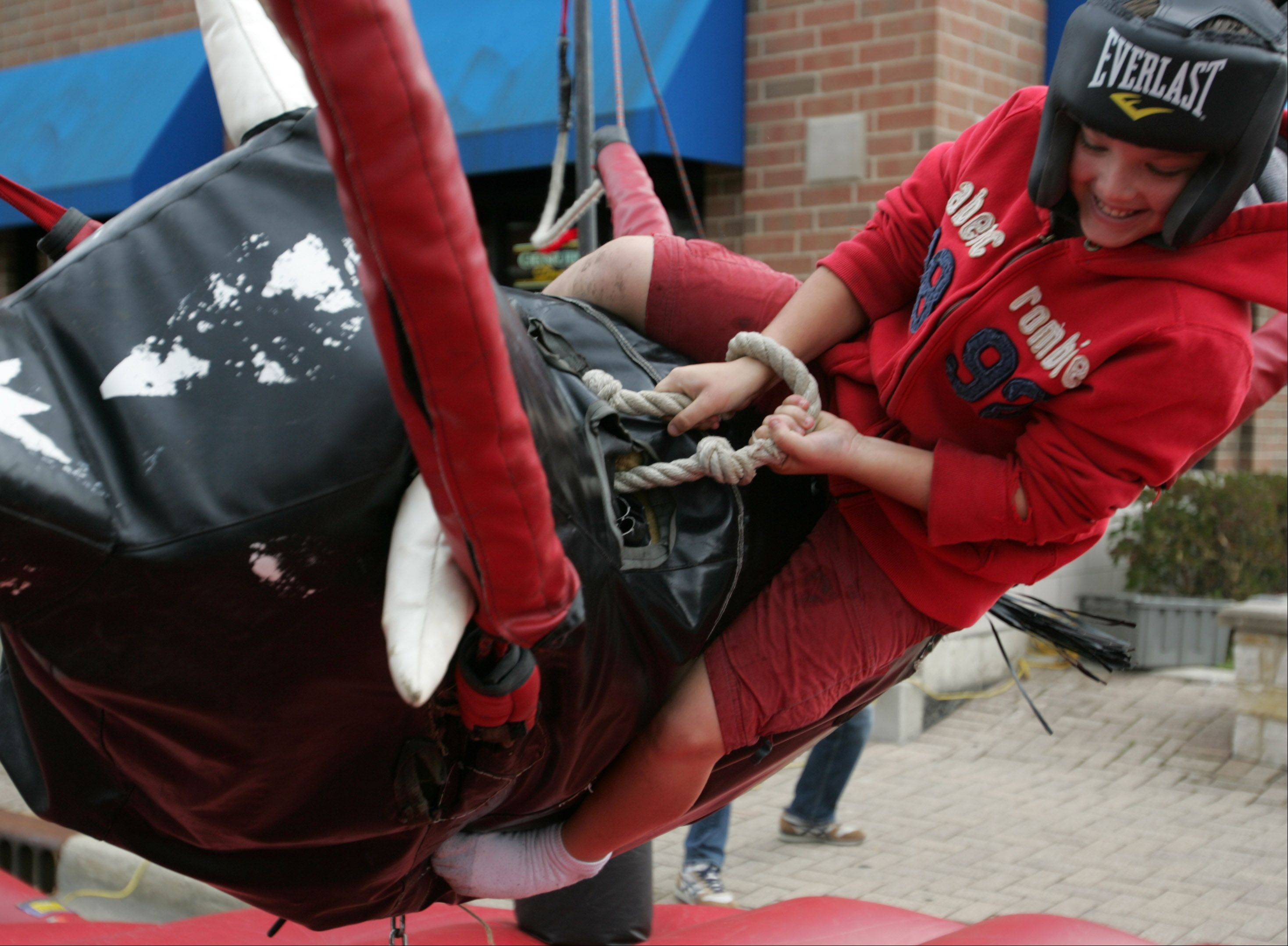 Keith Gill, 12, from Elmhurst tries to hold on while riding a fake bull during the Spooktacular Fall Festival Sunday in Lombard. Activities included a rock wall, carnival games, and trick-or-treating through local businesses.