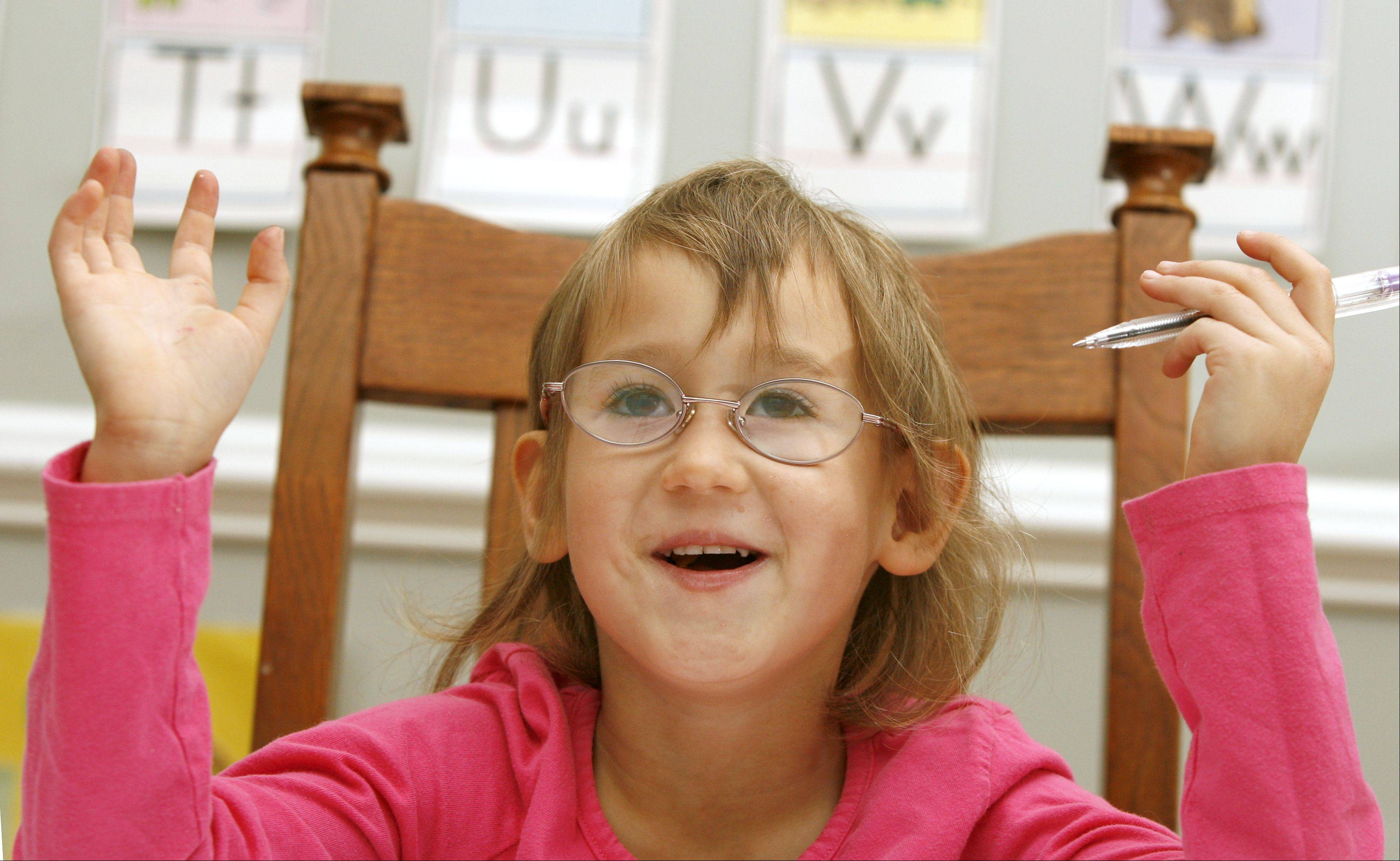 Sasha Wagner, 5, of Glen Ellyn, who was adopted from Russia and has fetal alcohol syndrome, creates artwork at the dining room table.