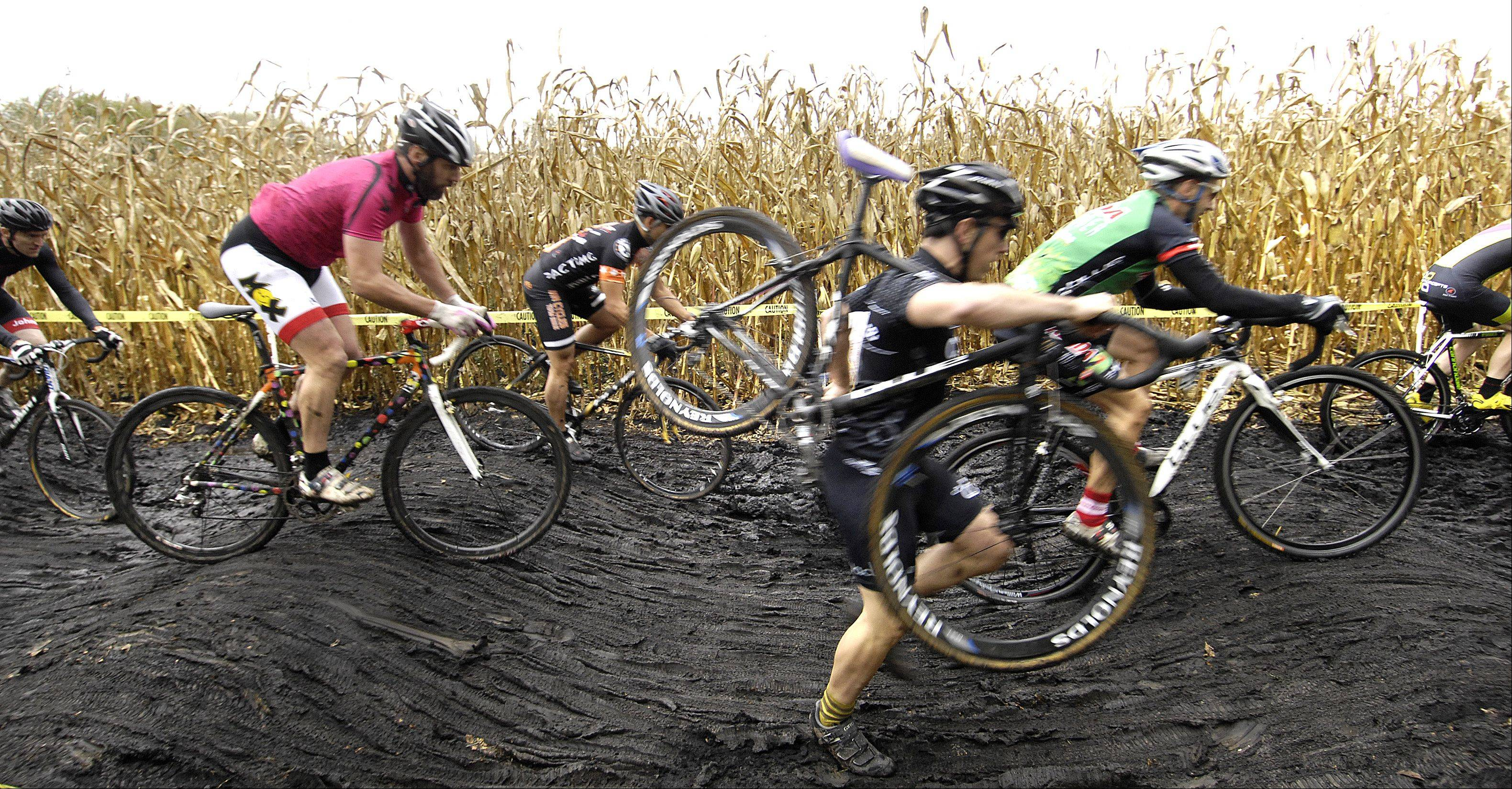Some racers carry their bikes through the dark mud Sunday in Carpenters Park.