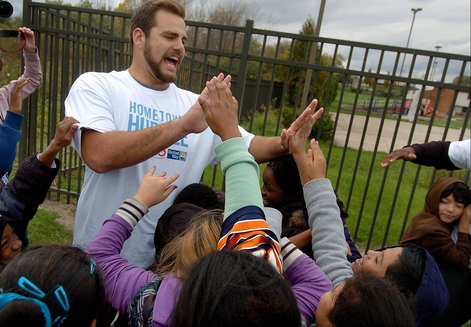 "Bears Offensive Tackle Gabe Carimi high fives the kids after playing ""Simon Says"" as members of the Chicago Bears and the United Way of Lake County hold a Hometown Huddle at Clearview Elementary School in Waukegan."