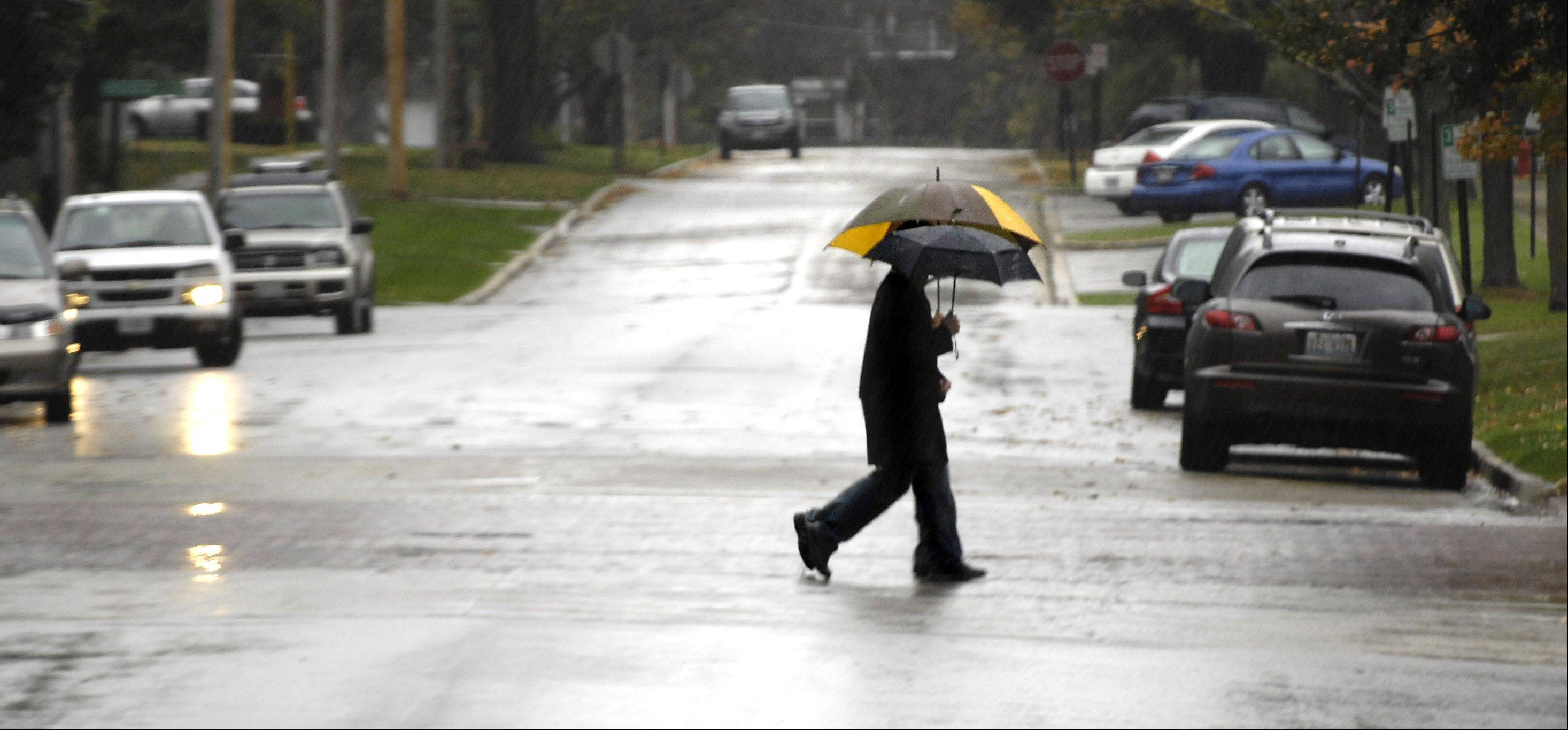 A pair of shoppers use umbrellas in downtown Geneva Wednesday.