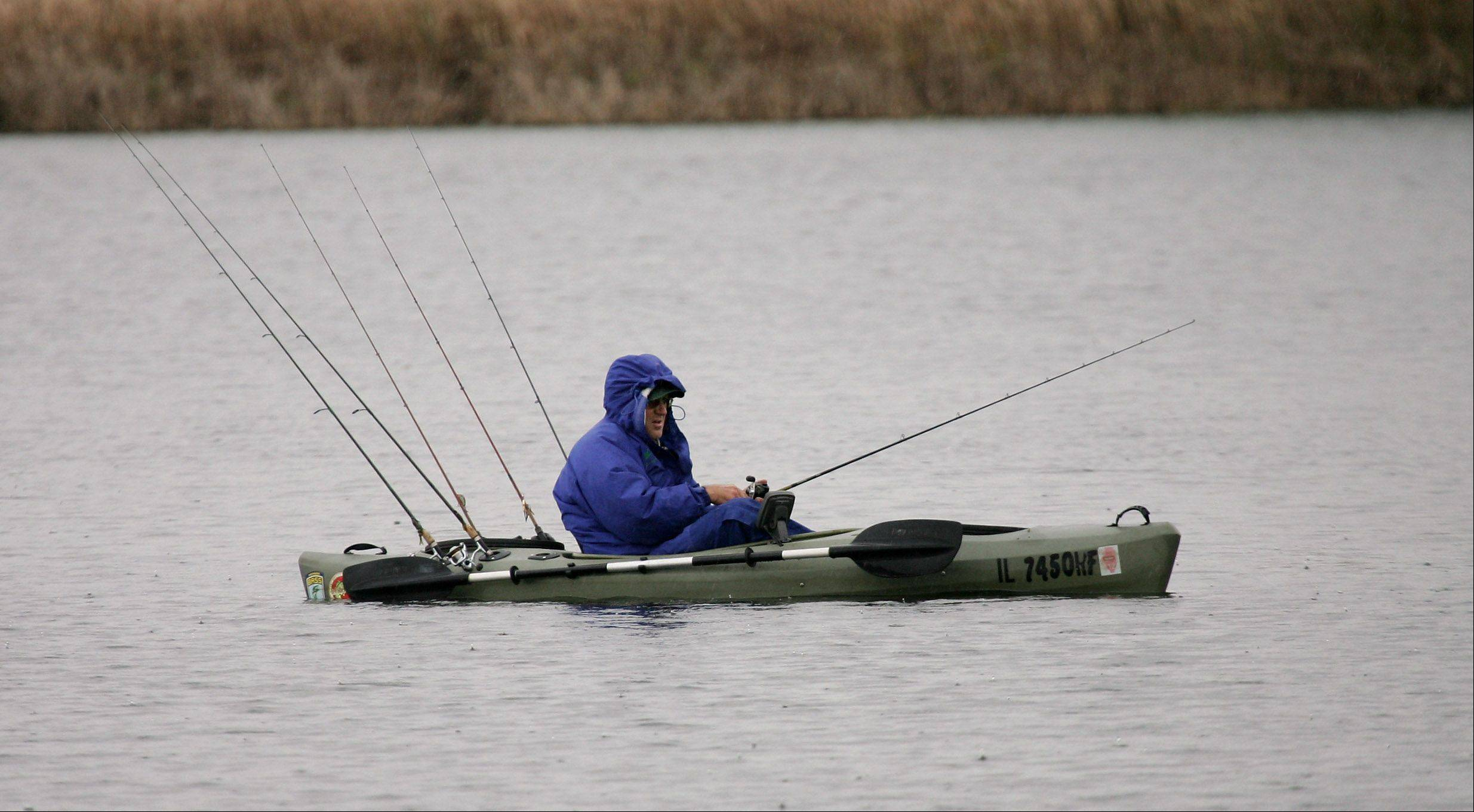 Rich Sazaras of Round Lake sits in the cold, rainy weather fishing from his kayak Wednesday on Butler Lake in Libertyville.