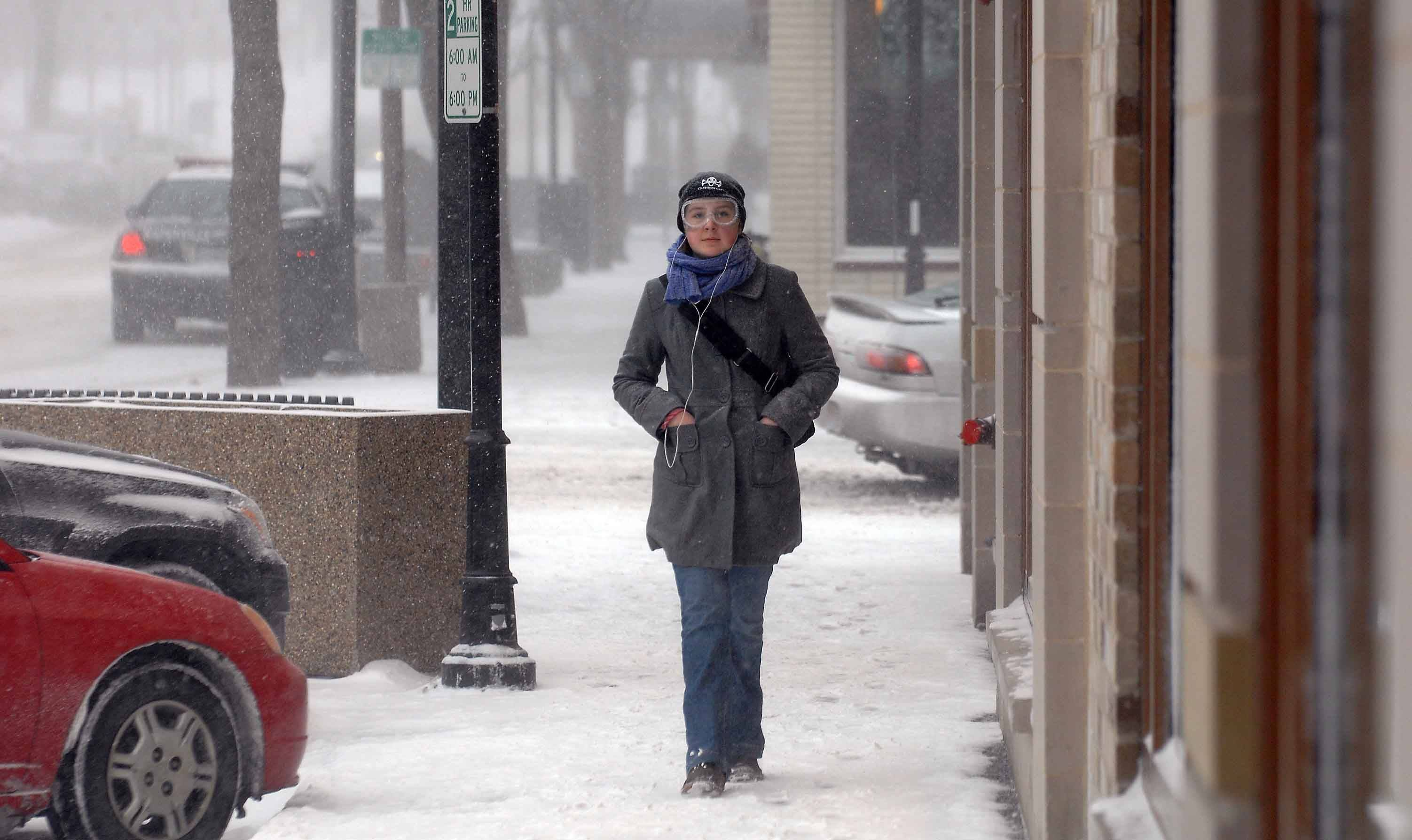 Julia Shaver of Naperville sports a pair of chemistry safety goggles during her walk in downtown Naperville during the February storm.