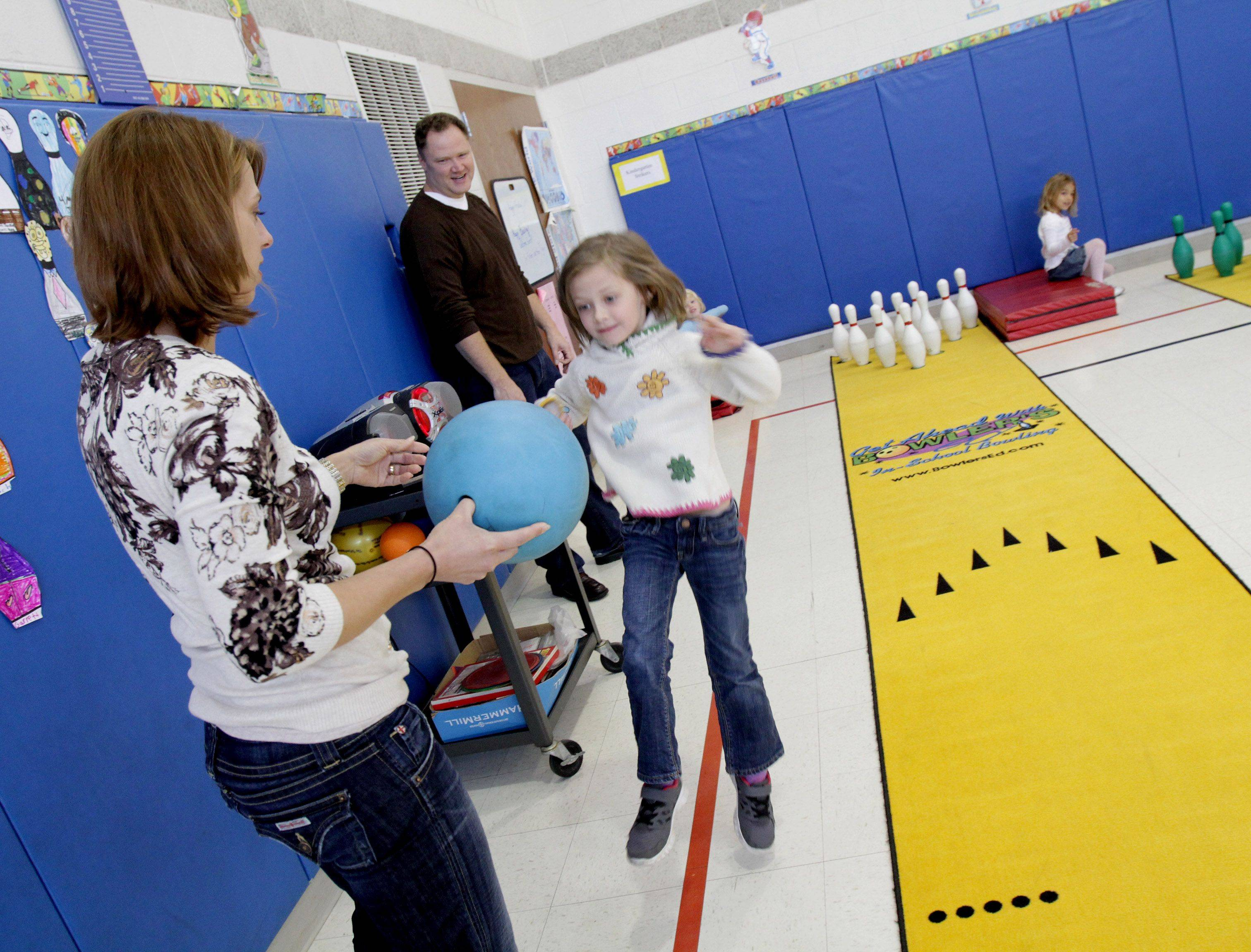 Kindergartner Jennifer Olson gets a ball as she bowls with her parents, Julie and Steve Olson, at Longfellow Elementary School in Wheaton. The bowling lanes, pins and ball were donated by Fox Bowl.