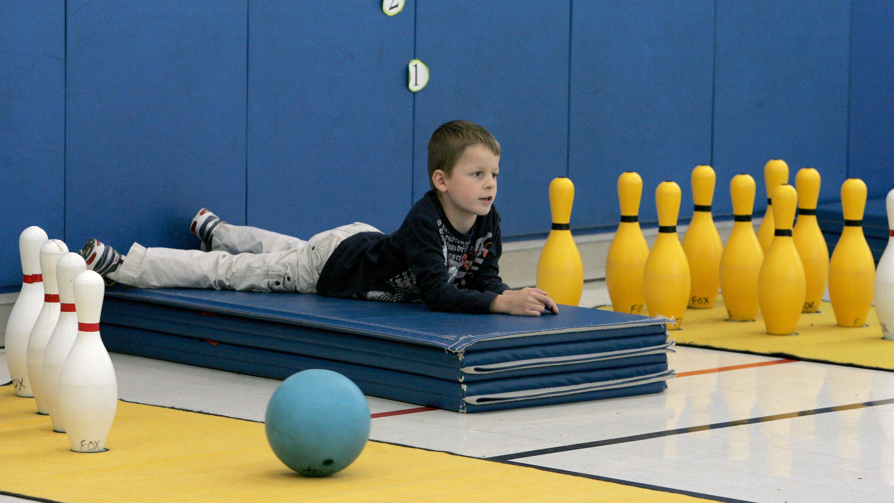 Kindergartner Micah Otts hangs out as he waits for his turn to bowl. Kids bowled with their parents at Longfellow Elementary School in Wheaton.