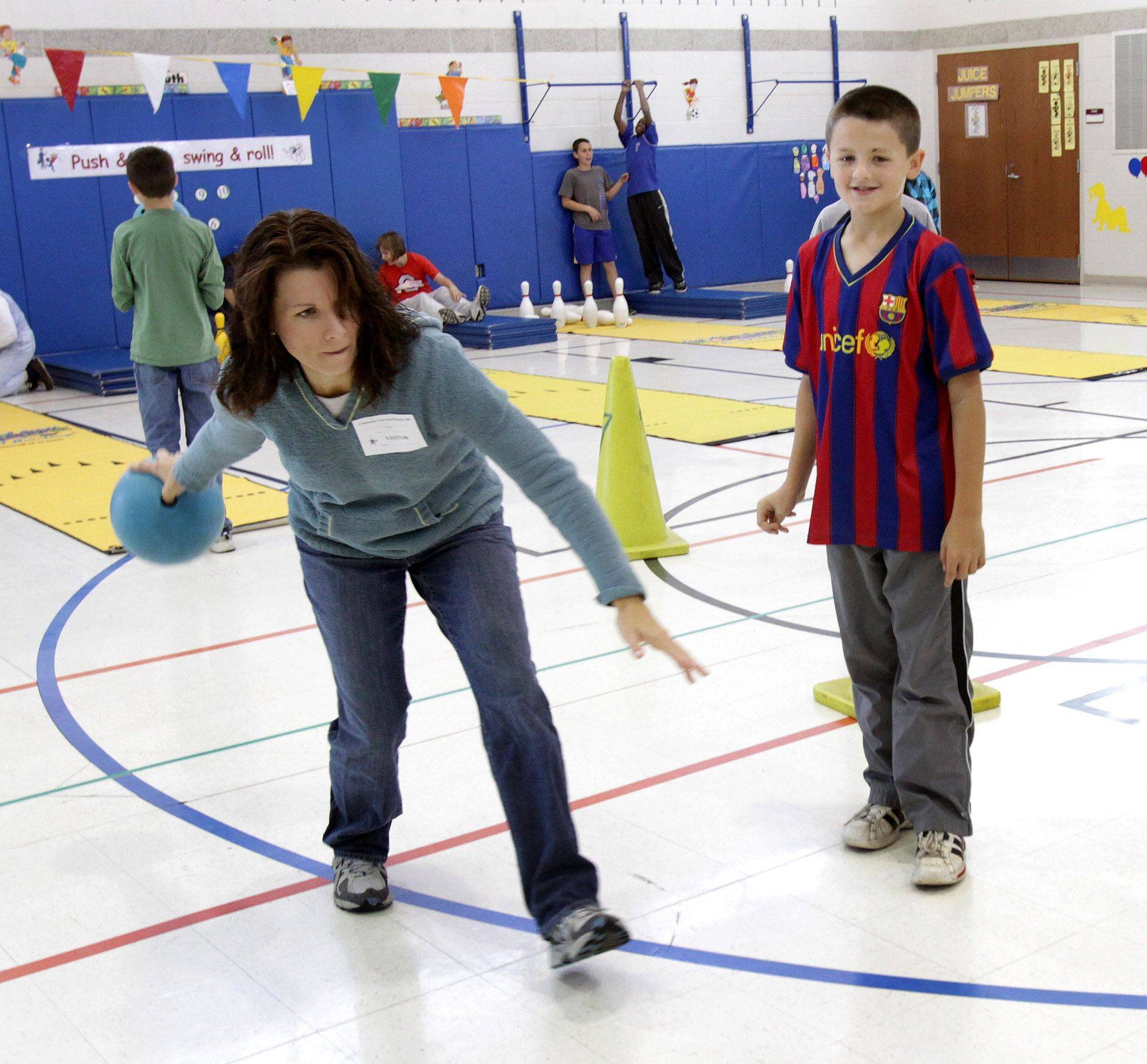 Elissa Schauer bowls as her fifth-grade son, Jacob, looks on.